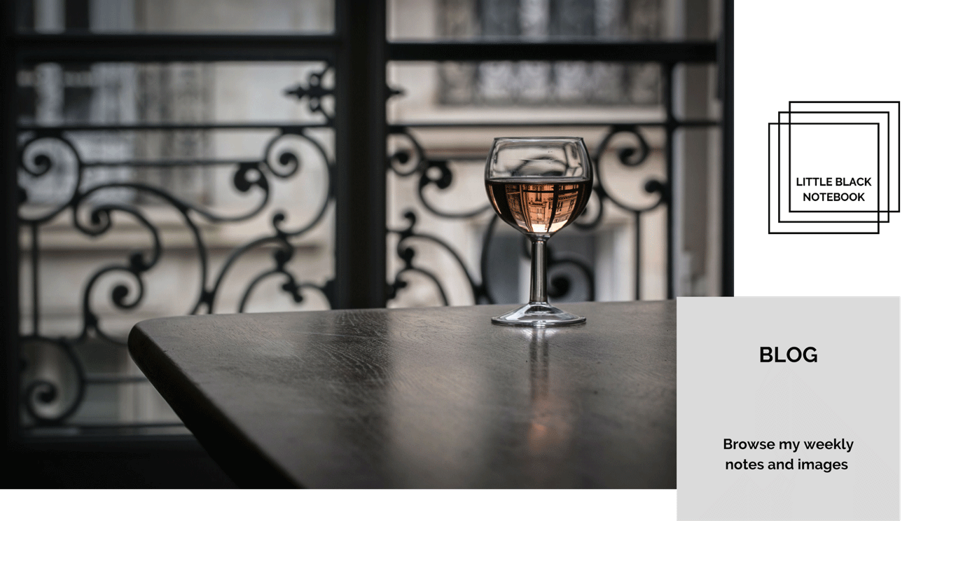 Link to blog page. Parisian view of a glass of rose wine on a table with Hausmannian buildings reflecting in it.