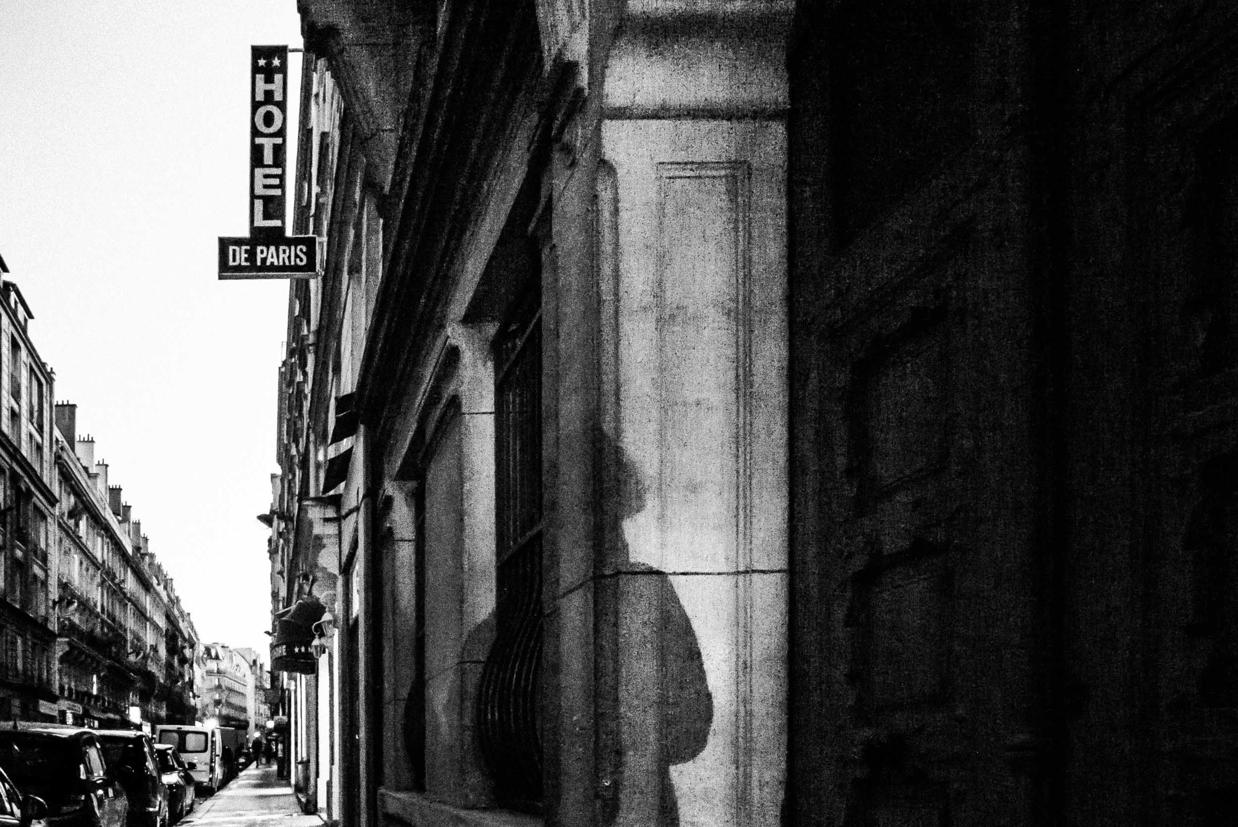 shadow of a woman on a building with Hotel de Paris sign. Paris street photography by Merja Varkemaa.