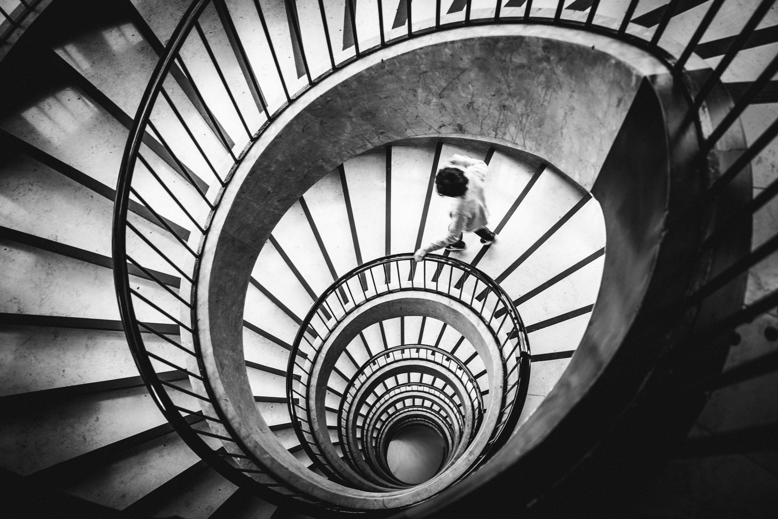 Boy running down spiral staircase by Merja Varkemaa