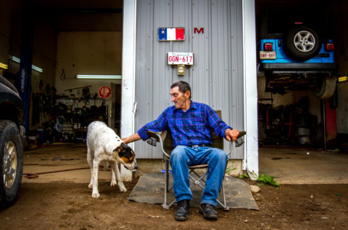 Marcel Richard sits outside of the mechanic shop that he and his family runs in their backyard, in Rogersville, NB. The land was purchased by Richard's father in 1938 and has remained in the family ever since.