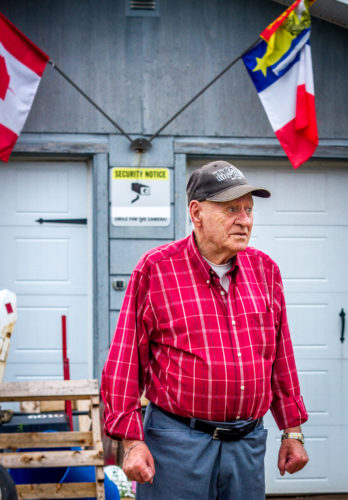 86-year-old Alyre Cormier stands in front of the garage where his son lives on his property in Memramcook, NB. Cormier has lived on the same street his whole life.