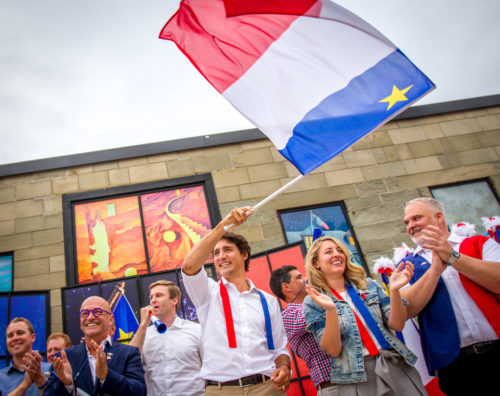 Justin Trudeau waves an Acadian flag alongside other dignitaries to begin the 2016 Tintamarre in Caraquet, NB.