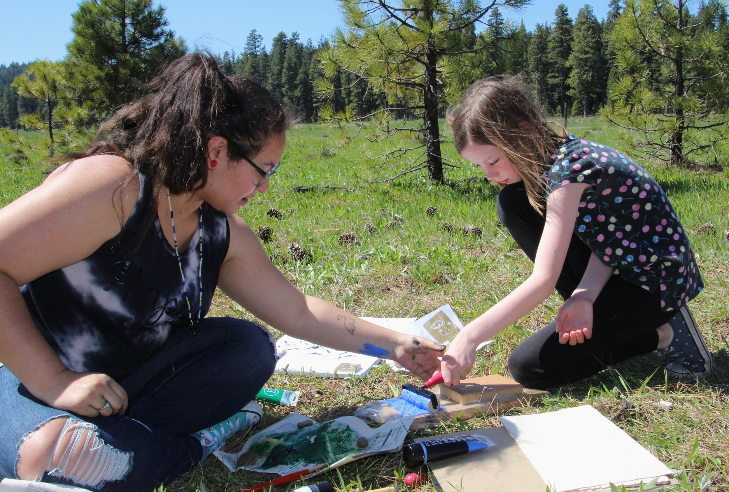 SOU Student Mentor Raven guides a student in some first-time print making with linoblocks.