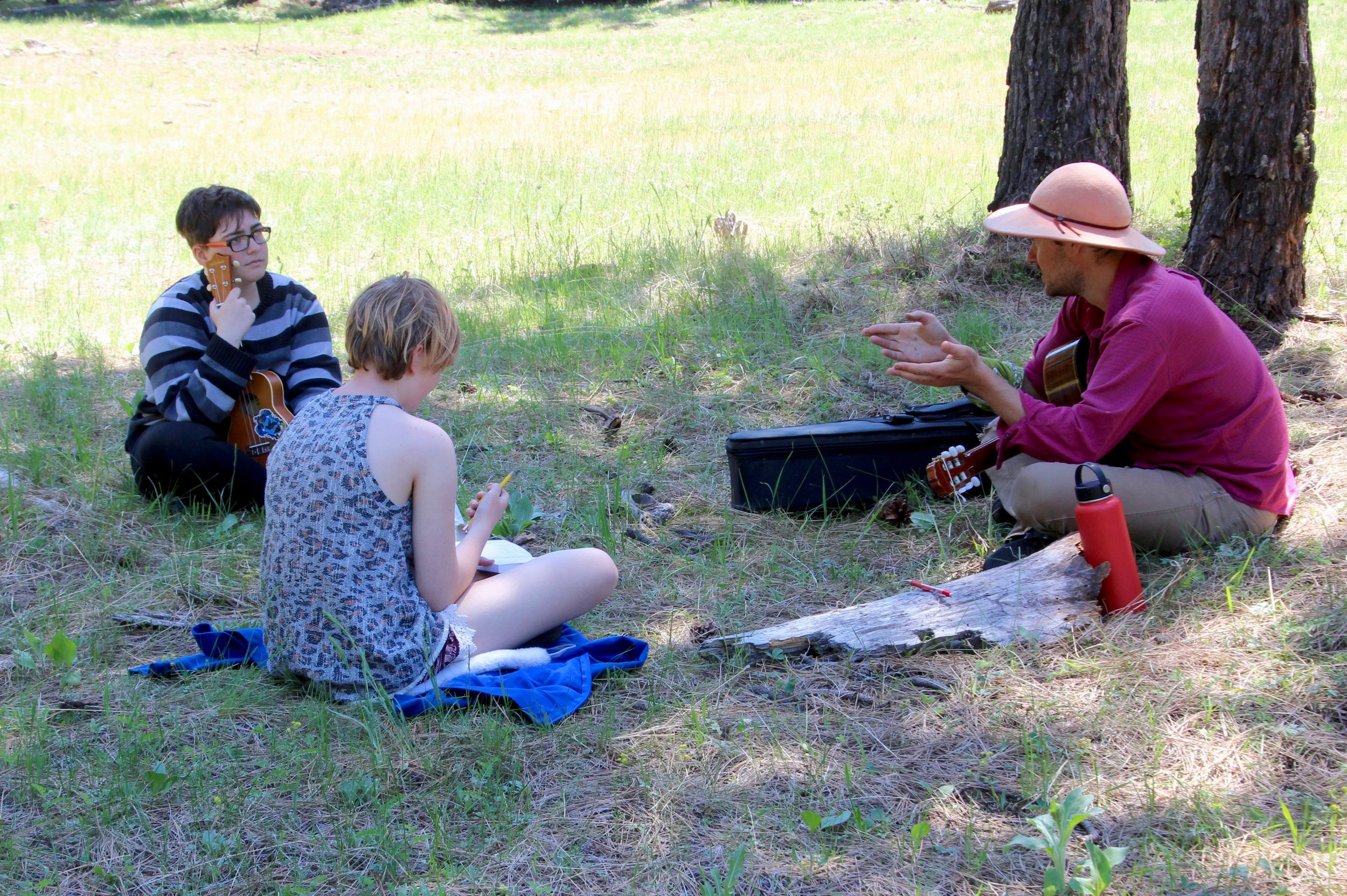 Daniel Sherriell, musician, discusses music theory and song writing in the shade of second growth forest. Check out our social media share of the song his students composed!