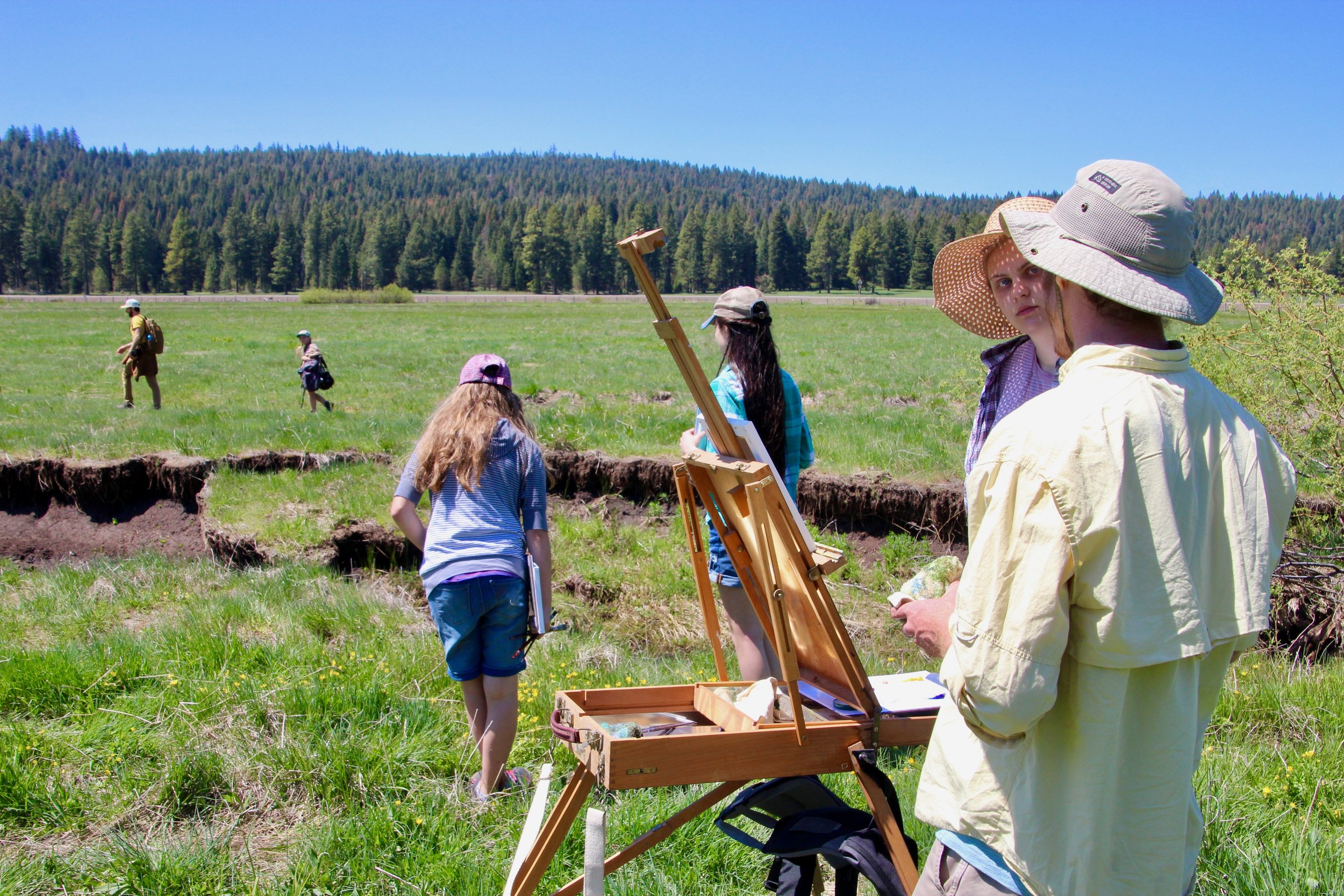 Along the eroded banks of the highly degraded Dead Indian Creek, artist Diamond Ferraiullo discusses landscape painting with HS Senior, while a photography group explores the meadow in the distance.
