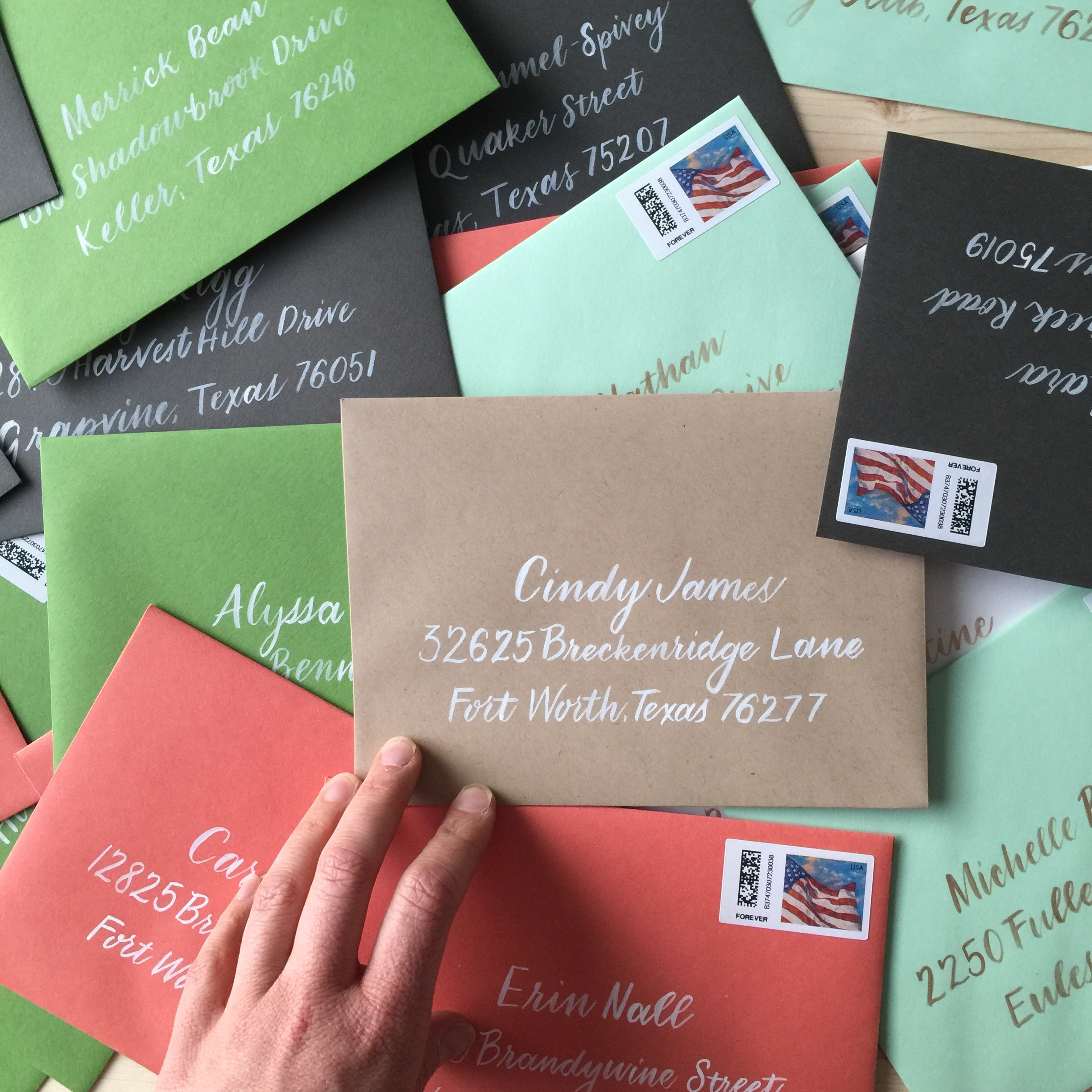 Colorful envelopes with white brush calligraphy addresses.