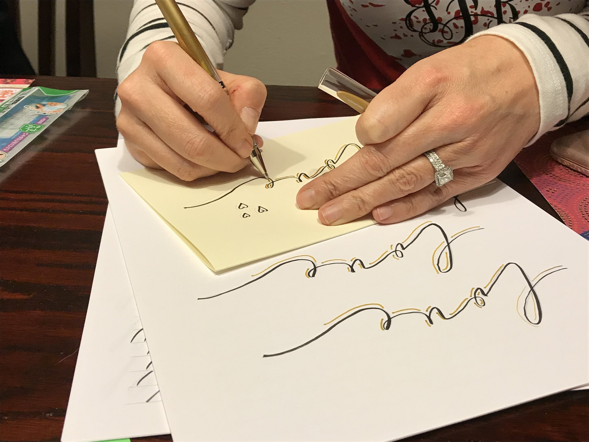 class participant practicing making love on a card in calligraphy