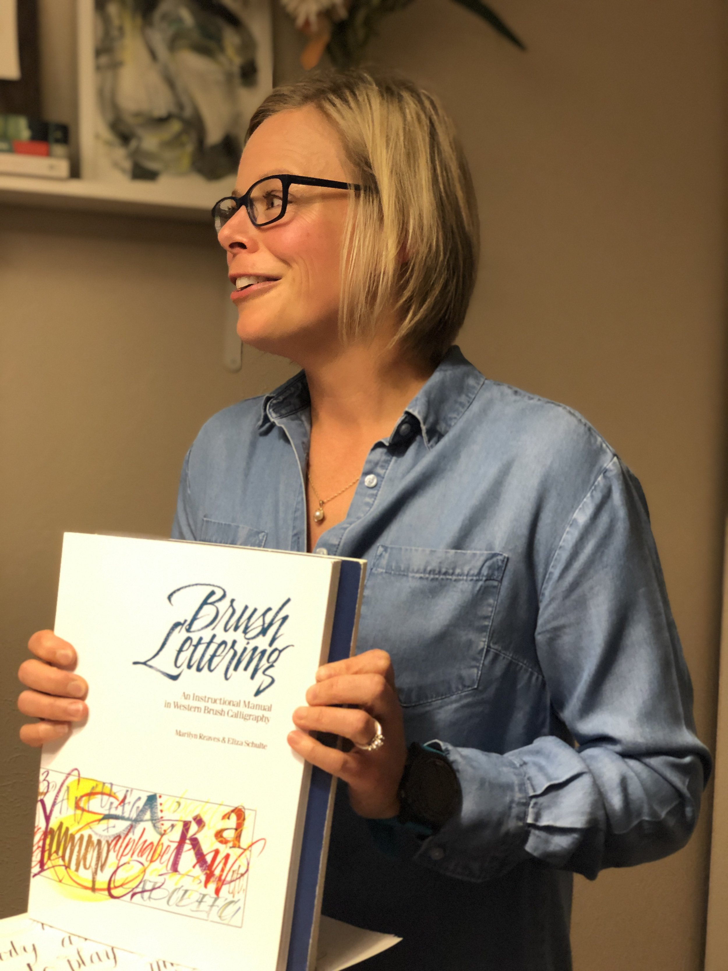 Michelle wearing a jean shirt, blonde hair, blue glasses holding brush lettering book.