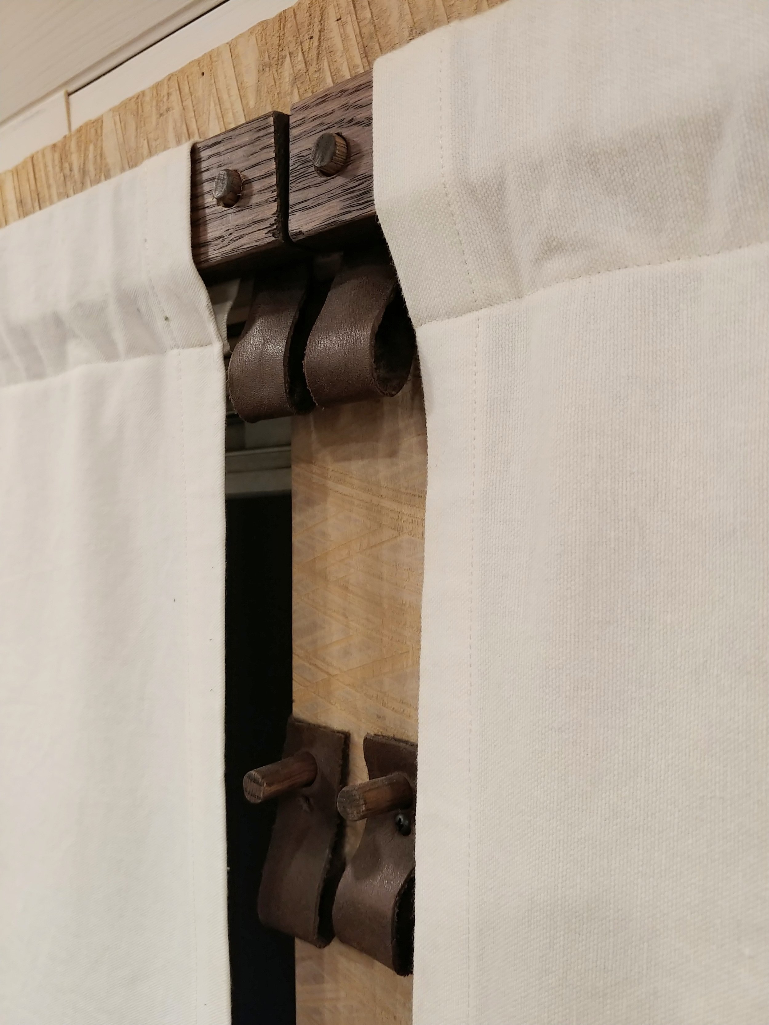 Upper and lower dowels give the top of the curtain two options for positioning. Leather loops allow the bottom of the curtain to be lifted to various heights.