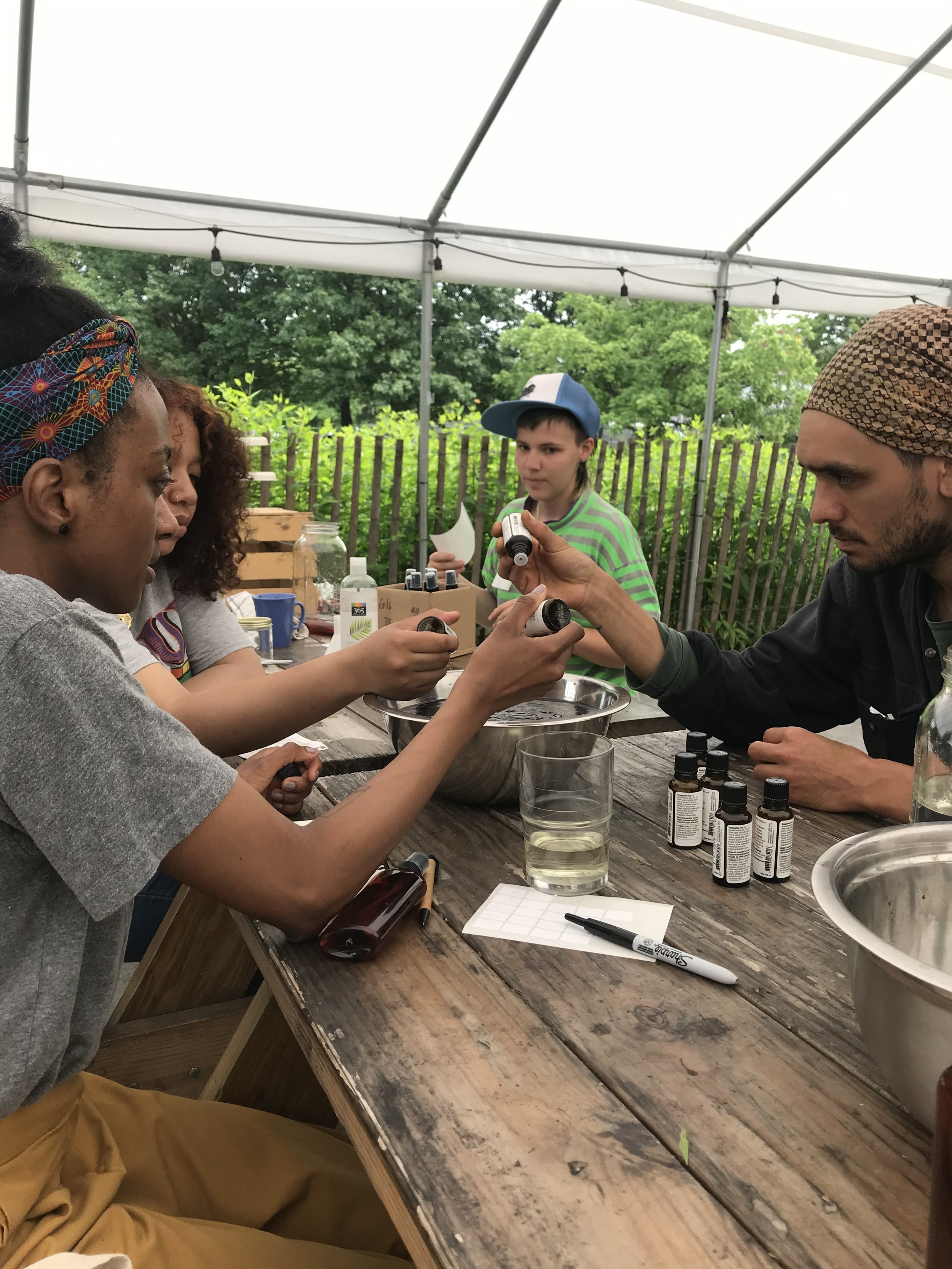 Look at the concentration on our faces as we are pouring the exact amount of essential oil drops needed!  Photo credit: David M. Alvarez