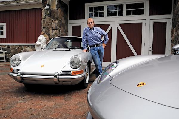 Michael J. Kitredge II standing next to two Porsche sports cars