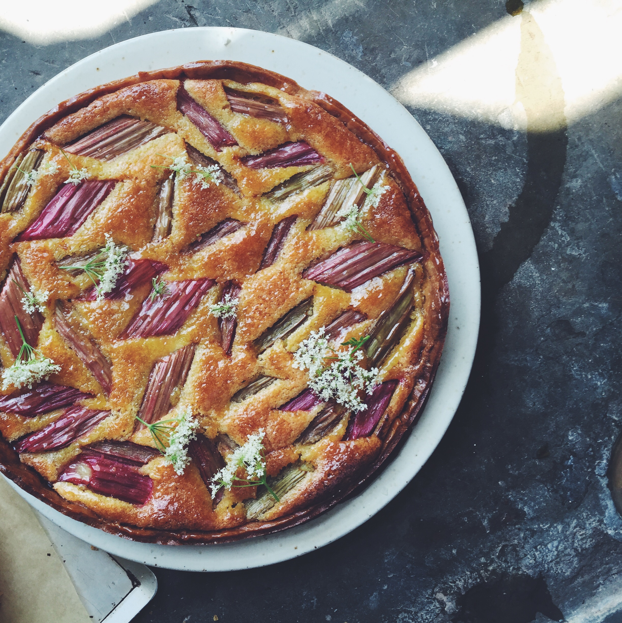 Rhubarb and almond tart with a layer of rhubarb and elderflower jam. Decorated with elderflowers.