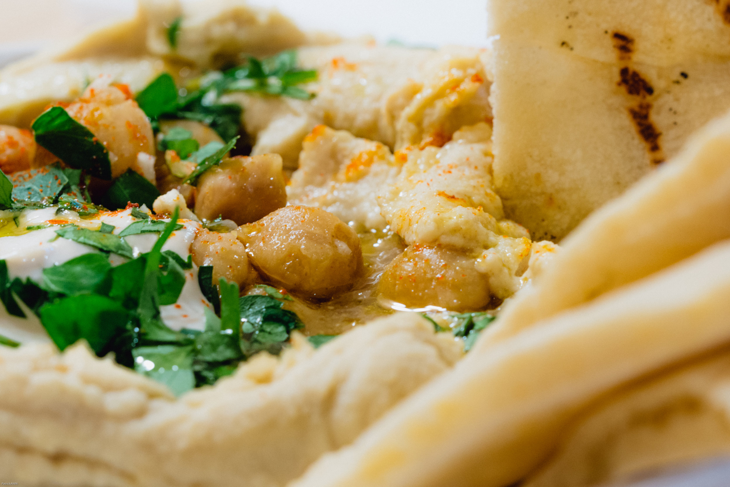 Hummus at Honey & Smoke is served with crispy chickpeas, fresh parsley, olive oil and green chili tatbila