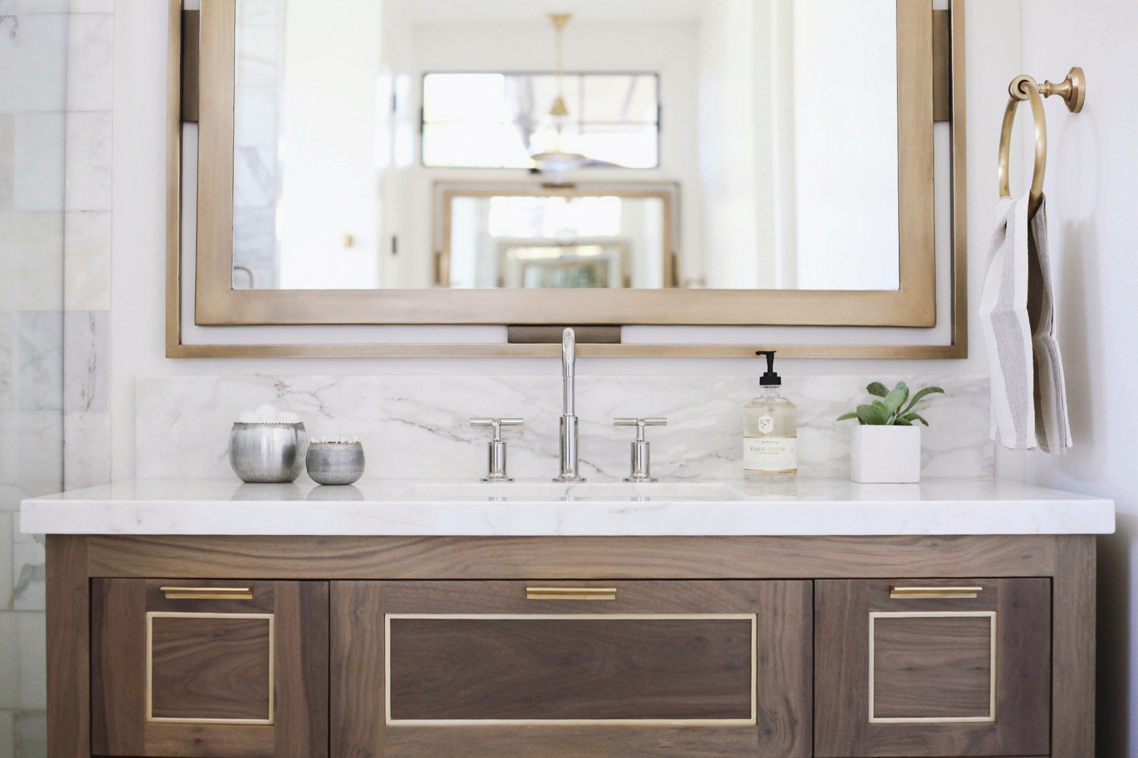 - The custom walnut and brass vanity in the master bath will forever be one of my favorite designs. The mixture of the classic, rich materials of brass and walnut complimented each other so well and Peterson Woodworks executed our designs beautifully.