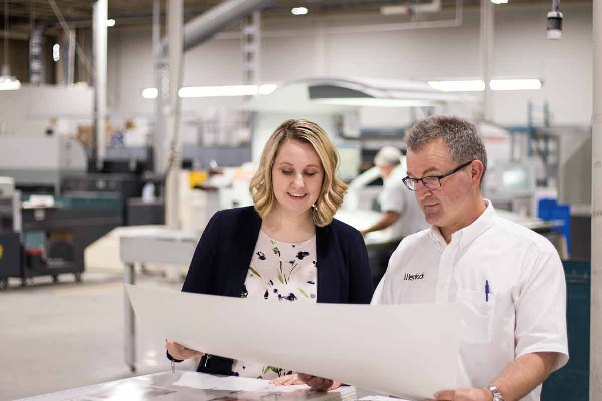Colleen Moyles, marketing coordinator, and Jeff Cooper, production manager, review a printed sheet on the floor of Hemlock's pressroom.  SUPPLIED
