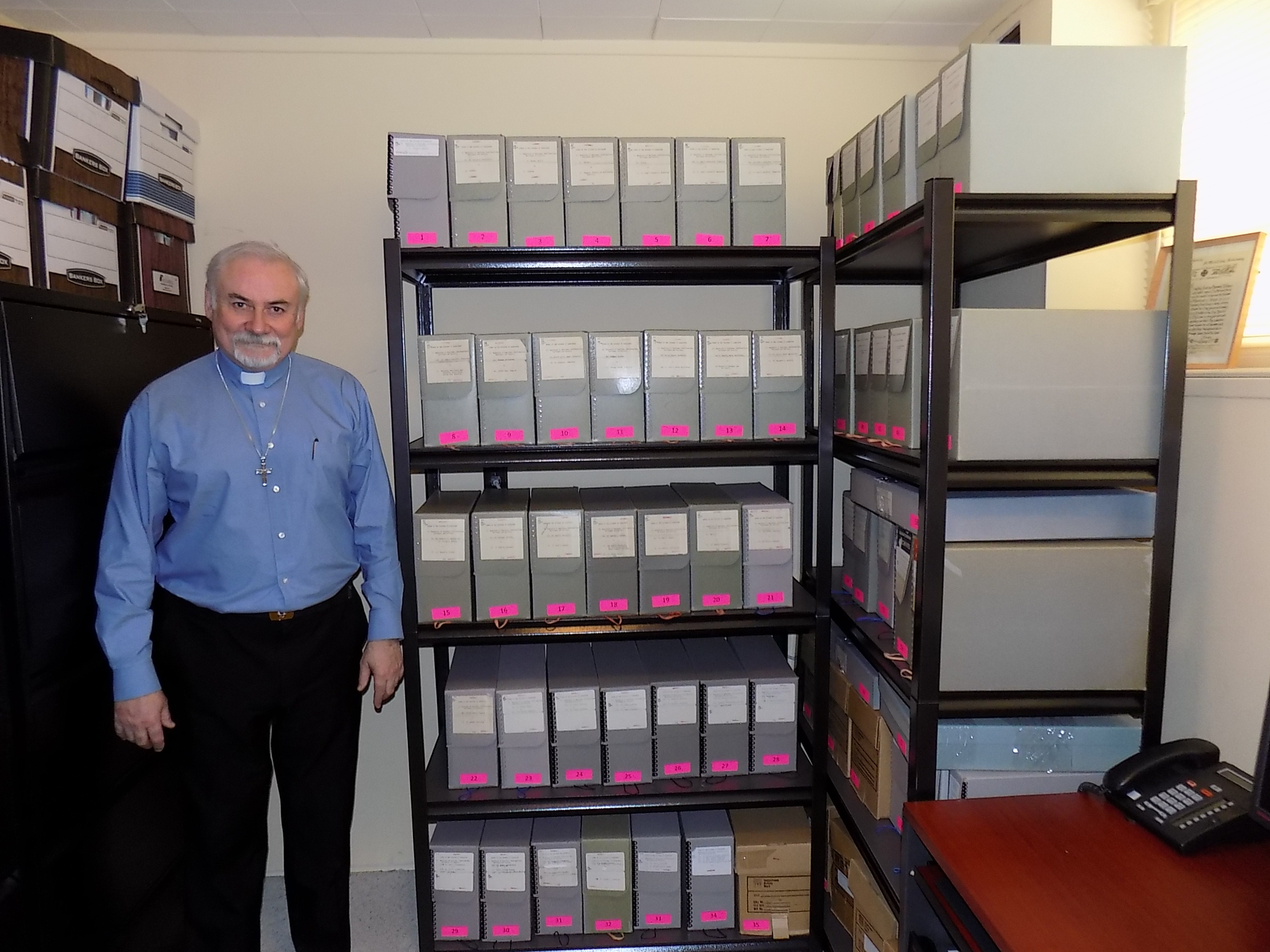 The Diocesan Archivist with some of the synod archives collection of registers of baptism, confirmation, marriage burial and church services stored within the synod office archive collection.  Photograph courtesy of The Rev. Peter Coolan