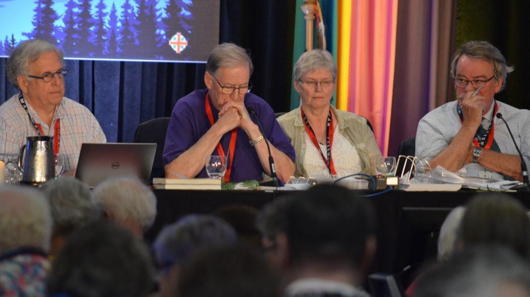 Primate Fred Hiltz and officers of General Synod share a tense moment of silence before results are revealed. Photo: Matthew Townsend