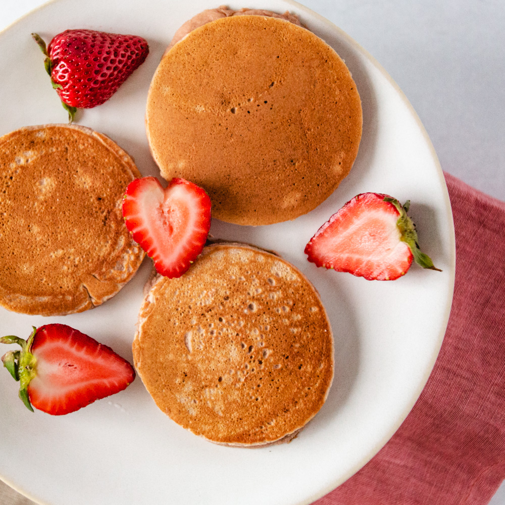 This easy, healthy strawberry pancake recipe comes together in a snap with help from your favorite mix! Click to learn how! Recipe by  Fresh + Lively , a healthy lifestyle blog. #breakfast #mornings #paleo #maplesyrup #kids #treats #fun #dairyfree #summer #brunch #berries #cooking #pancakes #freshfruit #sweets #cinnamon #glutenfree #paleo