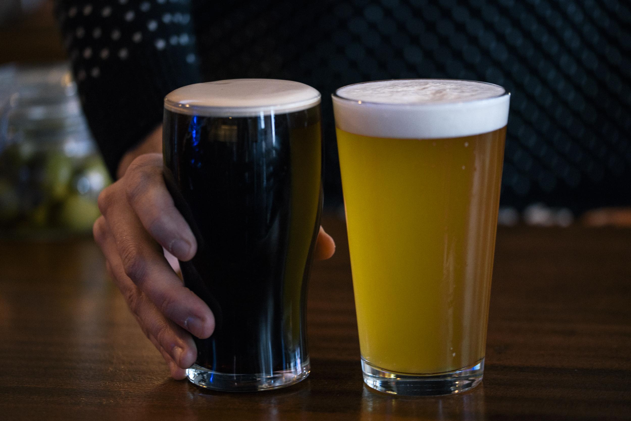 two pints of draft beer in pint glasses, one dark beer and one light beer