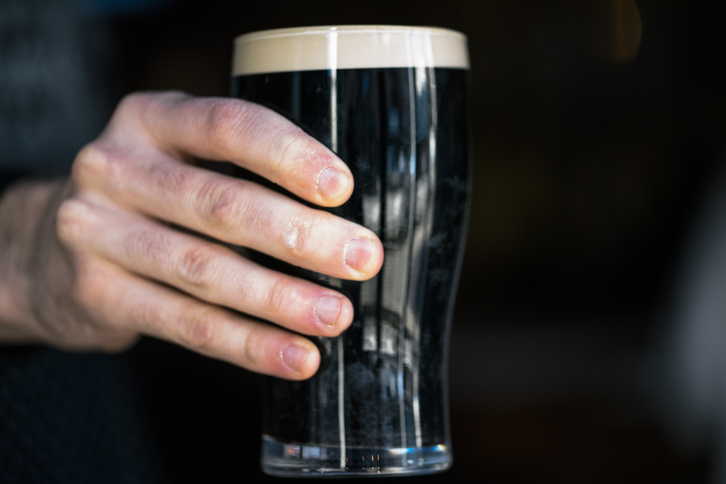 hand holding up pint of guinness beer