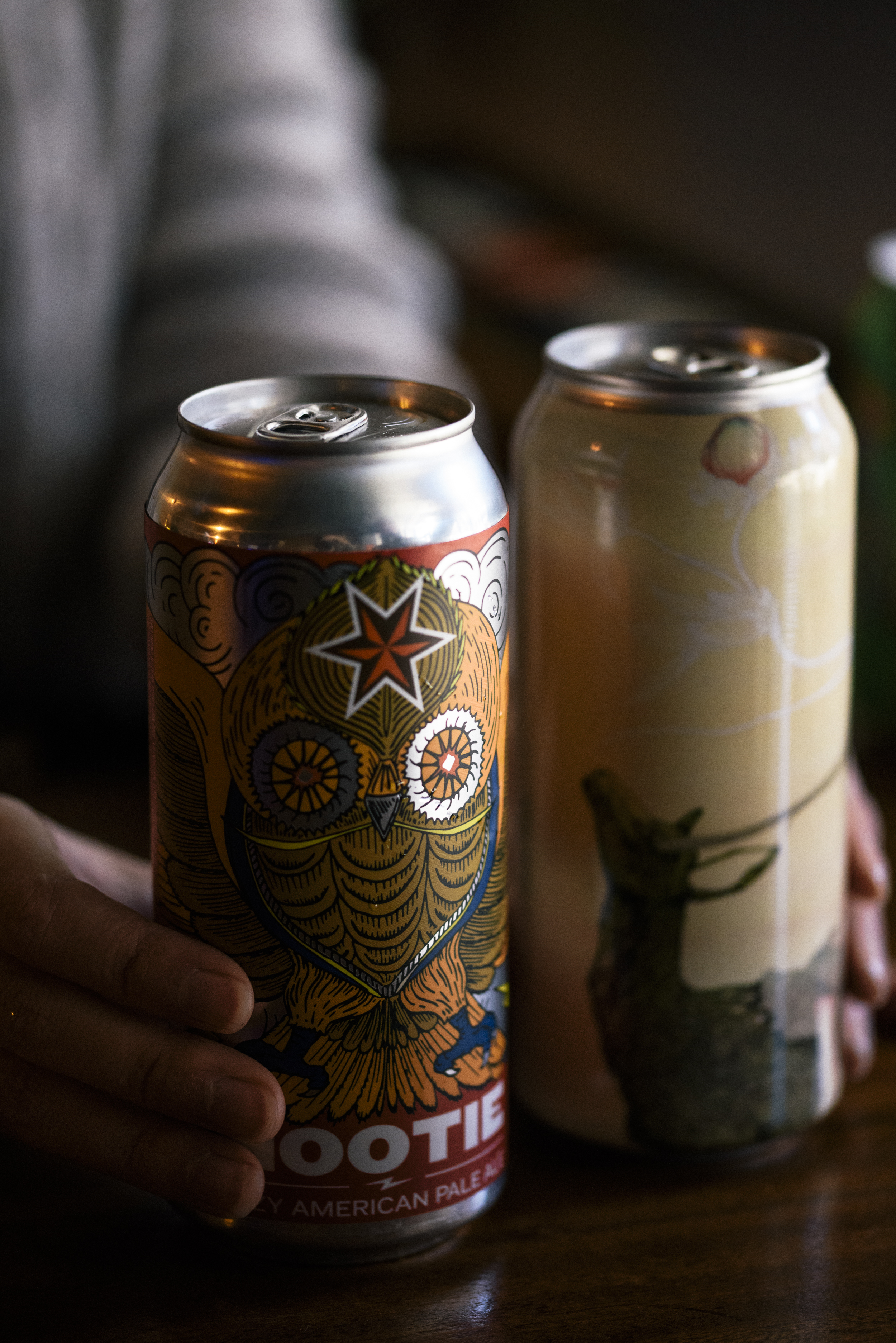 close up of bartender hands with two cans of beer