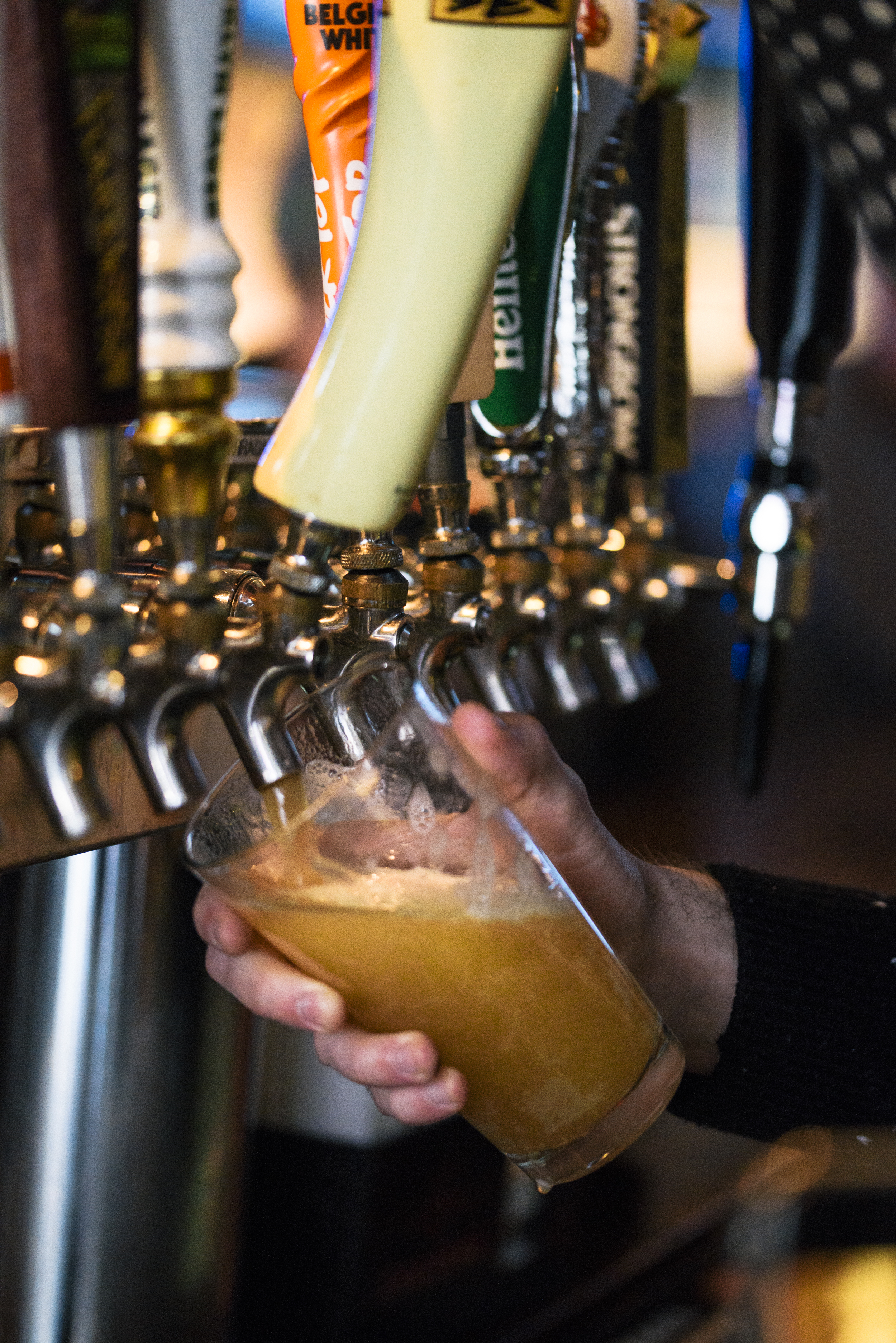 close up of bartender pouring a light draft beer into glass pint glass