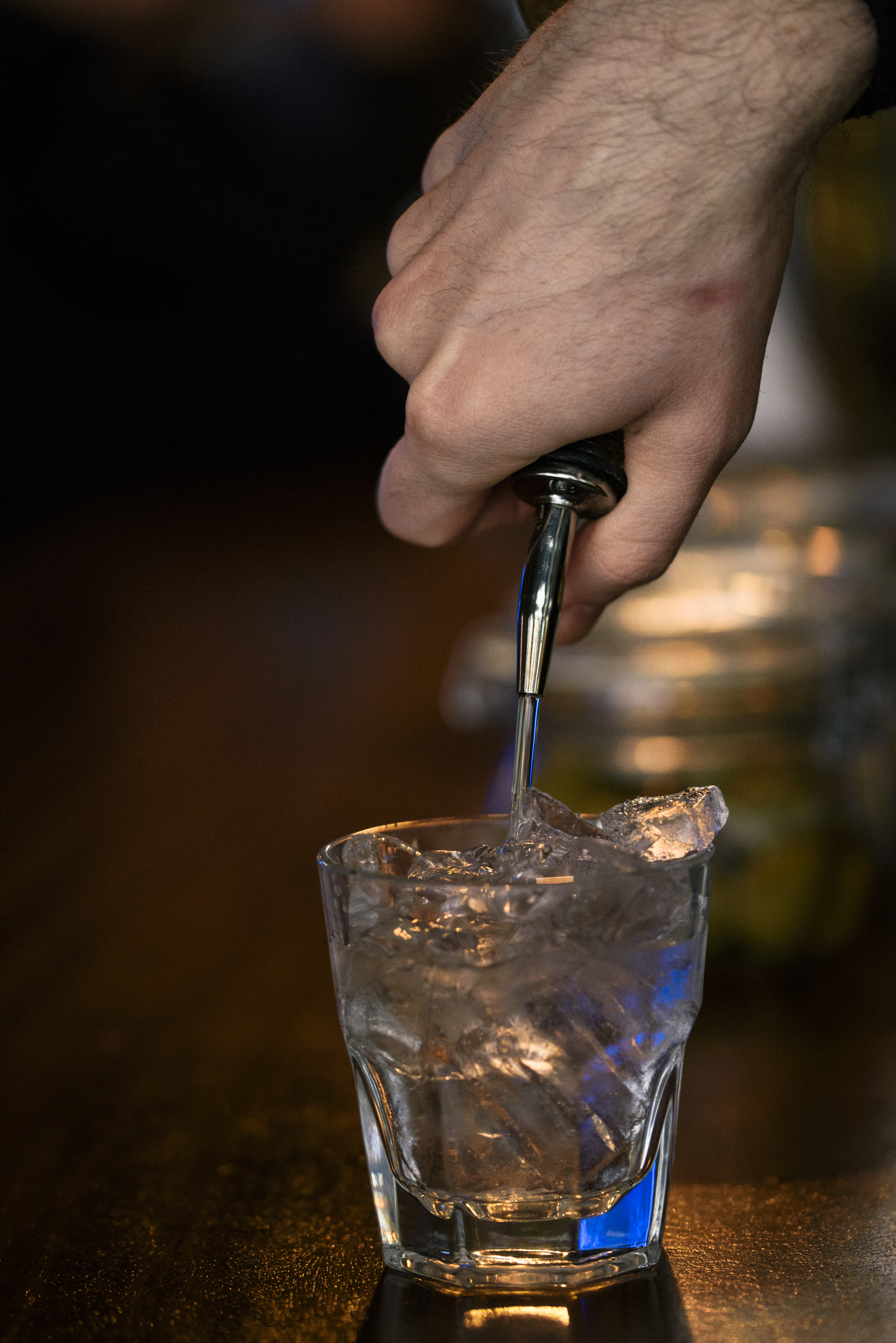 hand of bartender pouring vodka into short glass with ice