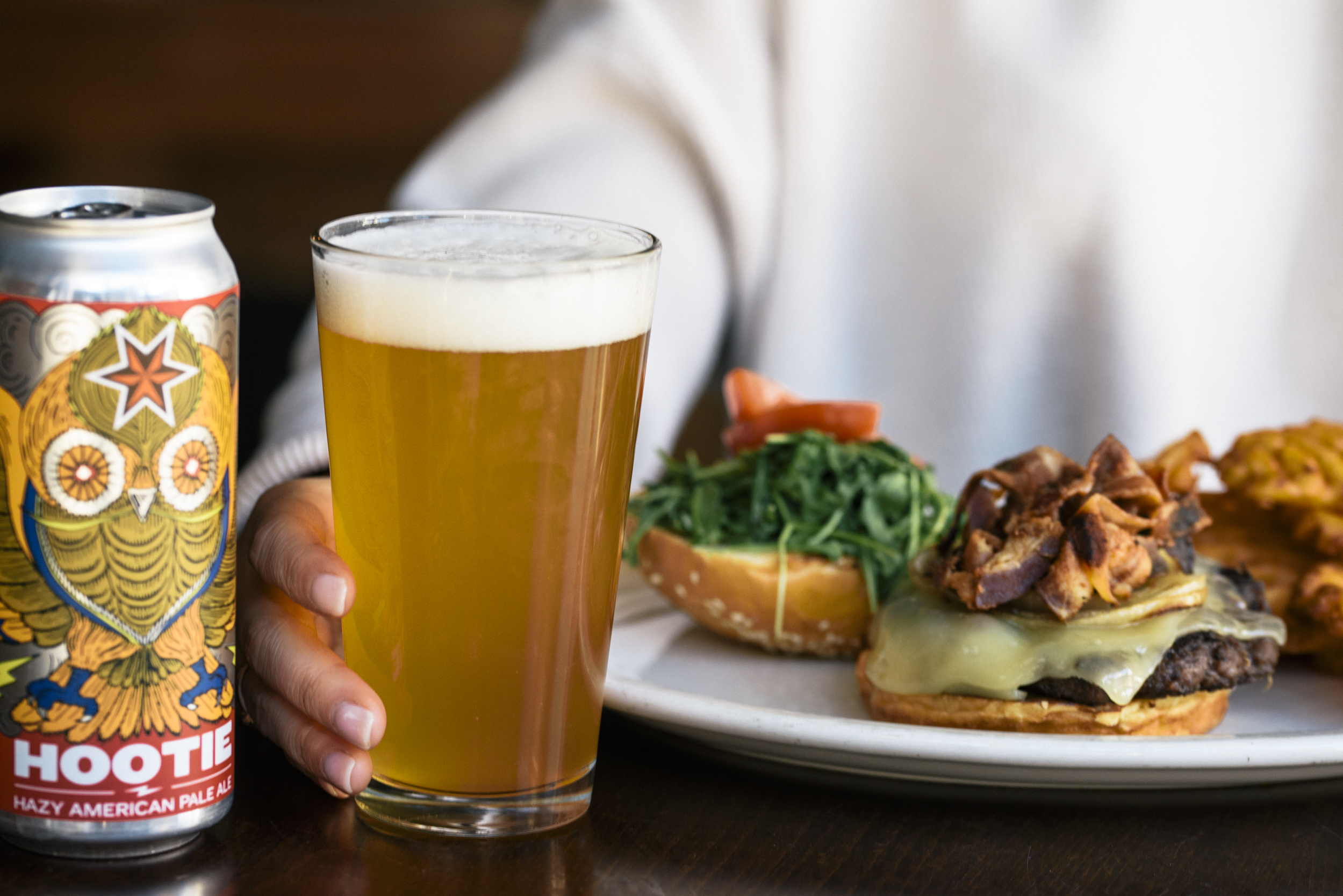 a close up of a woman with open bacon cheese burger on a plate infront of her with a pint of freshly poured Hootie beer next to plate and can of beer on left side of photo