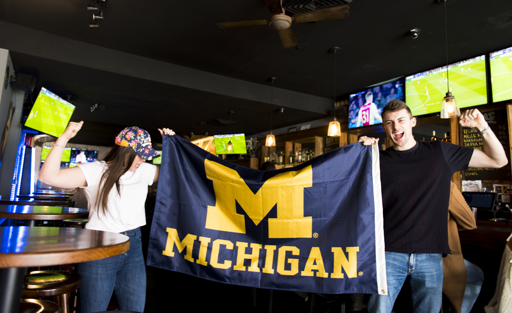 fans-holding-and-cheering-michigan-state-flag.jpg