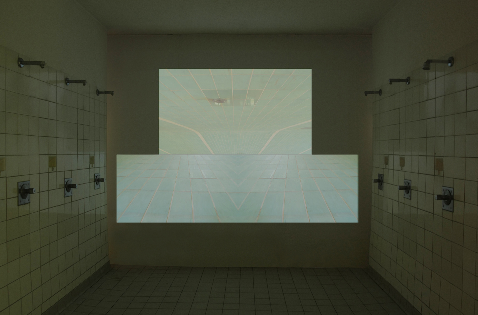 kacheln, three-channel video projection, 6:09 min., 2011  (installation view)  In kacheln the camera speeds over the tiled floor of an empty swimming pool. It moves at different angles and perspectives making the tile pattern appear like a perspective grid, merging it into one dragging surface, as well as fragmenting it with a kaleidoscopic effect to create new spatial situations. The camera explores the swimming pool following the three tracks and the limiting lines that before determined the movement of the swimmers.