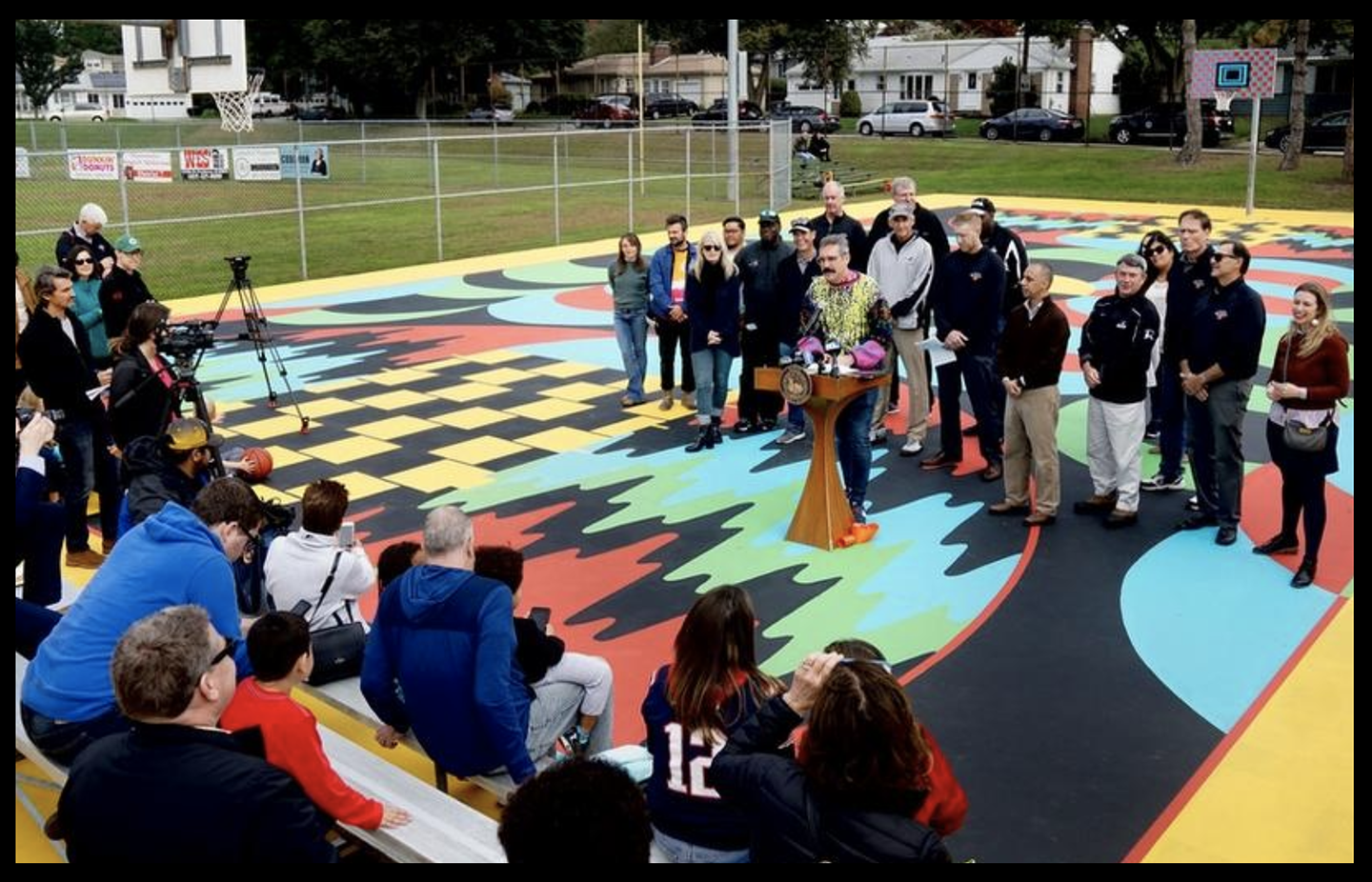 Artist Jim Drain addresses the crowd at the grand opening celebration and unveiling ceremony of My HomeCourt at Fargnoli Park in Providence. [Image Credit: The Providence Journal / Kris Craig]