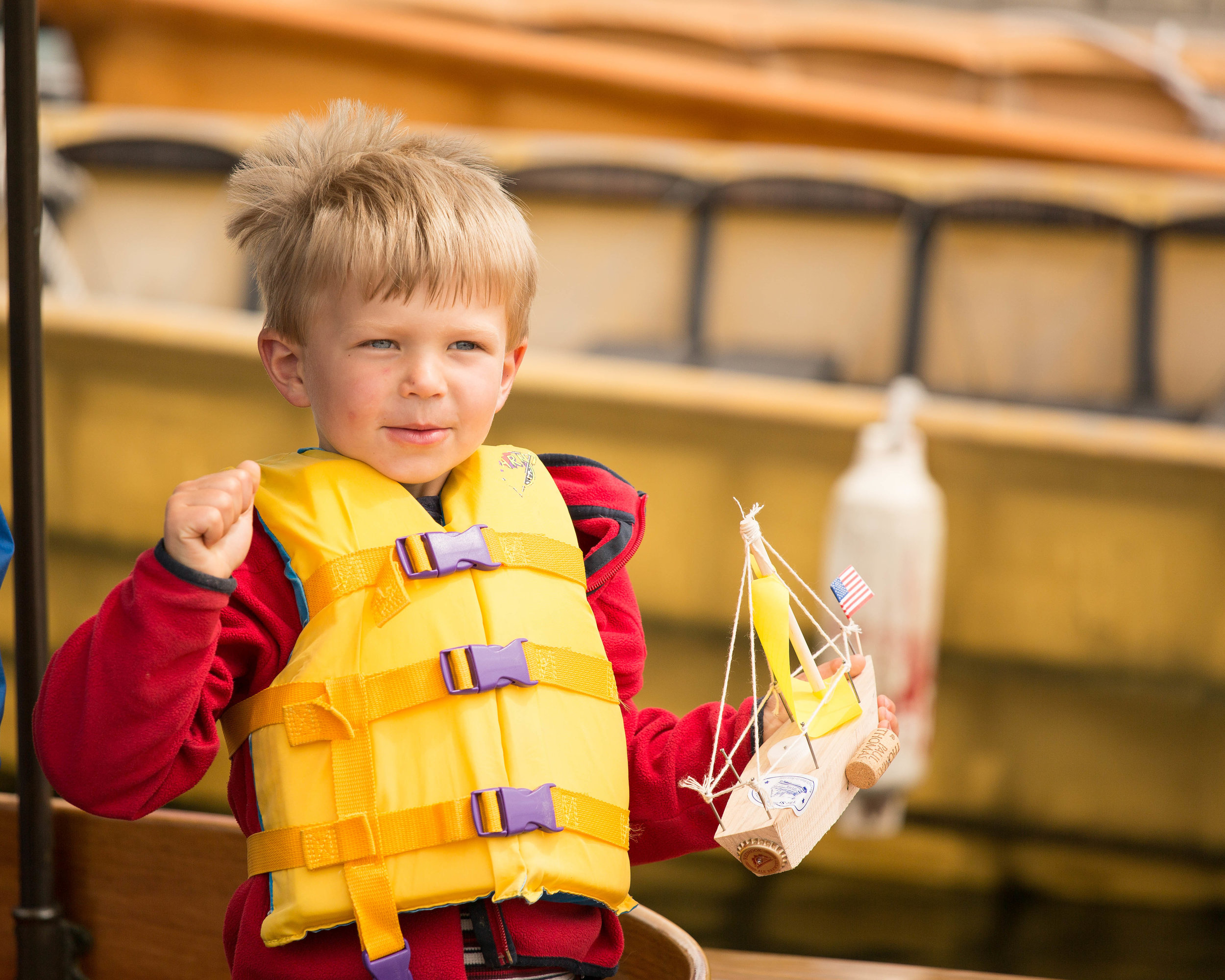 Kid in yellow life jacket and red sweatshirt holding a wooden toy boat