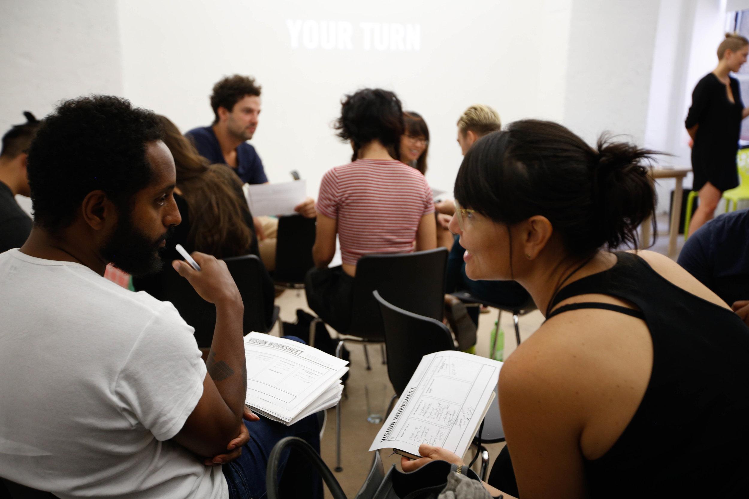 Workshop participants in conversation. Links to Program Overview.