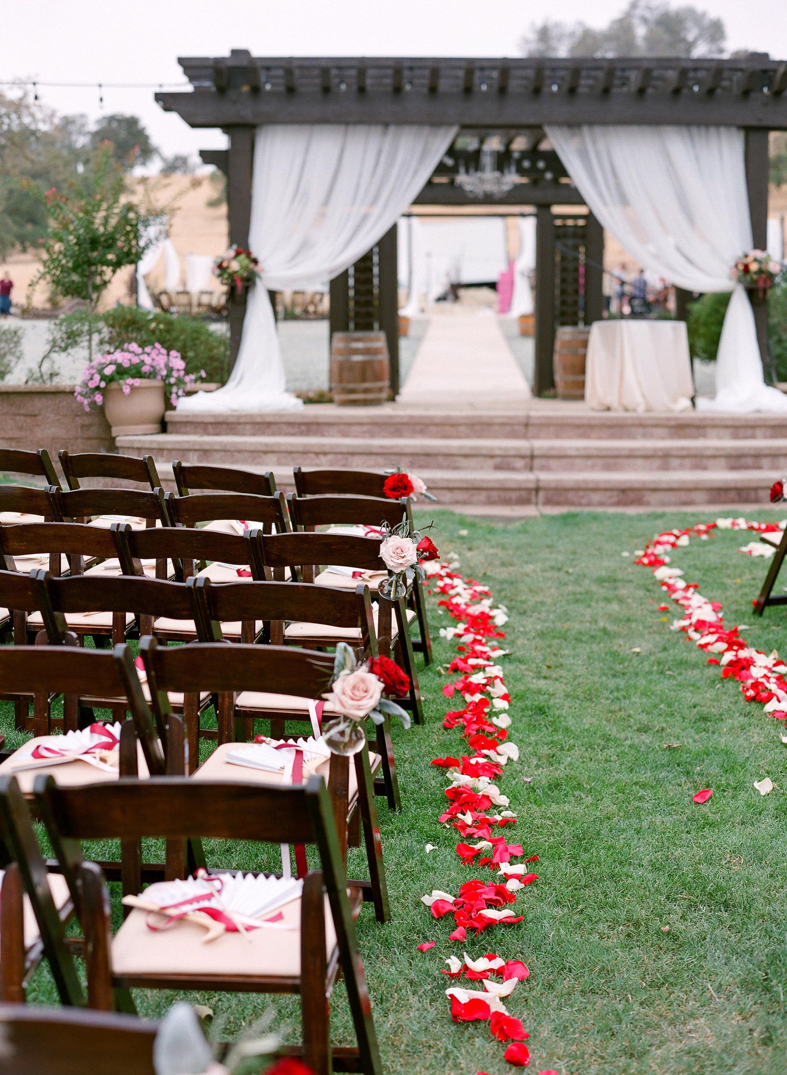 Wedding_Aisle_Arrangements_Petals_Draping_Red_Gold_Pink_Rancho_Victoria_Vineyard_Northern_California.jpg