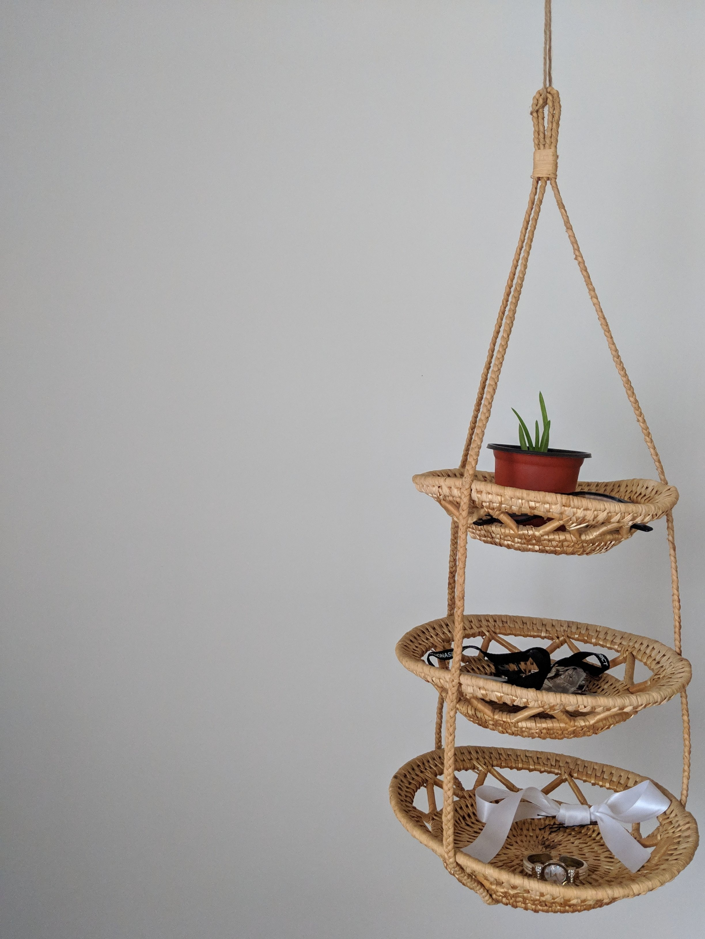 """10. Woven Shelving - Salvation Army, $1.99: I think this is supposed to be for hanging fruit, but it works quite well as a """"grab and go"""" station, hanging from my clothing rack. I keep my accessories, work badges and glasses here and I added a small aloe plant I was recently gifted!"""