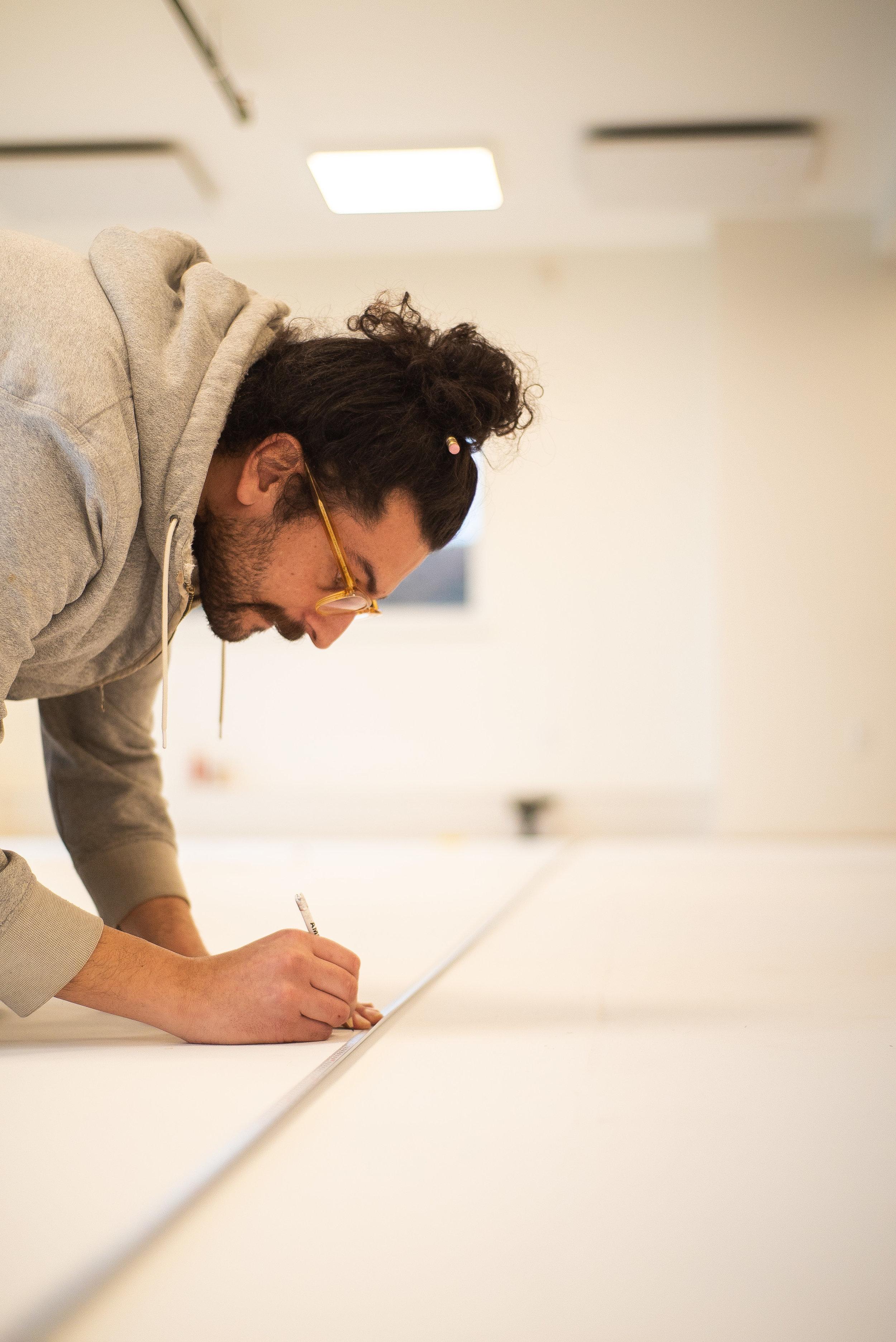 """João Bentes, mark making and measuring the  linha de flutuação , or """"Load Waterline"""" on the lofting floor. Photo: Chris Battaglia"""