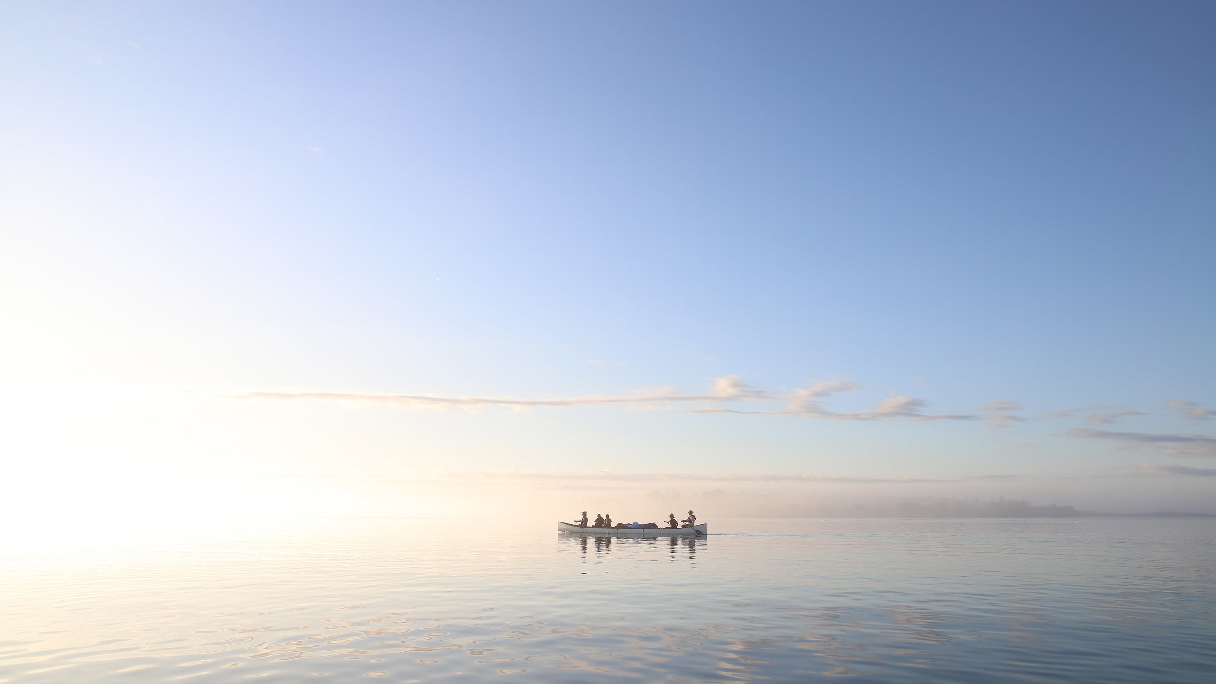 Artists paddling the 31' canoe (built by Mike Maybury) in early morning on Penobscot Bay.  Photo: Brian Wasser