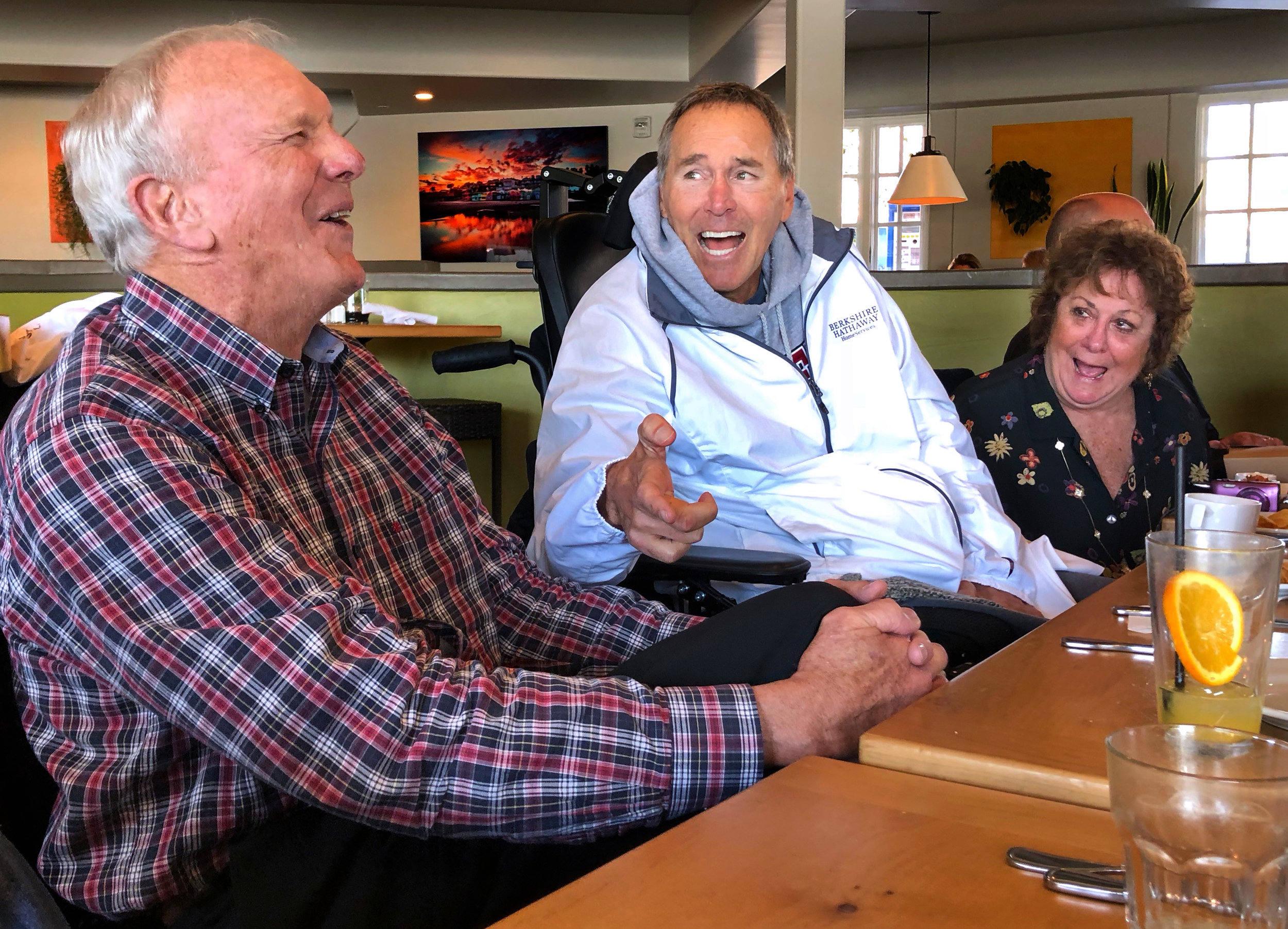 Sam Wyche, Dwight Clark, and Nicole Gisele laugh during lunch in Capitola, California, on February 27, 2018.