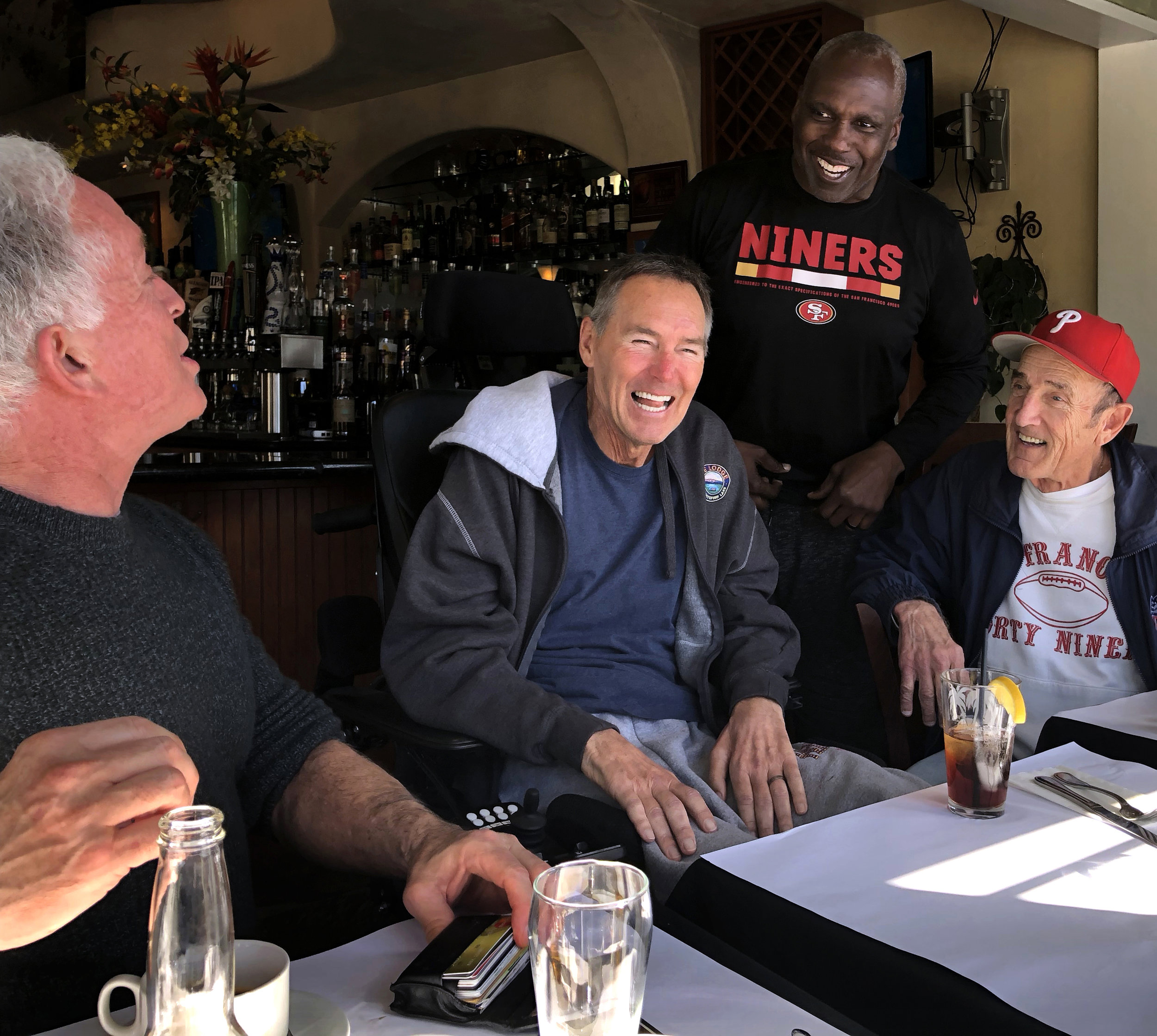 Mark Ibanez, Dwight Clark, Guy McIntyre, and Michael Zagaris laugh during lunch in Capitola, California, on February 13, 2018.