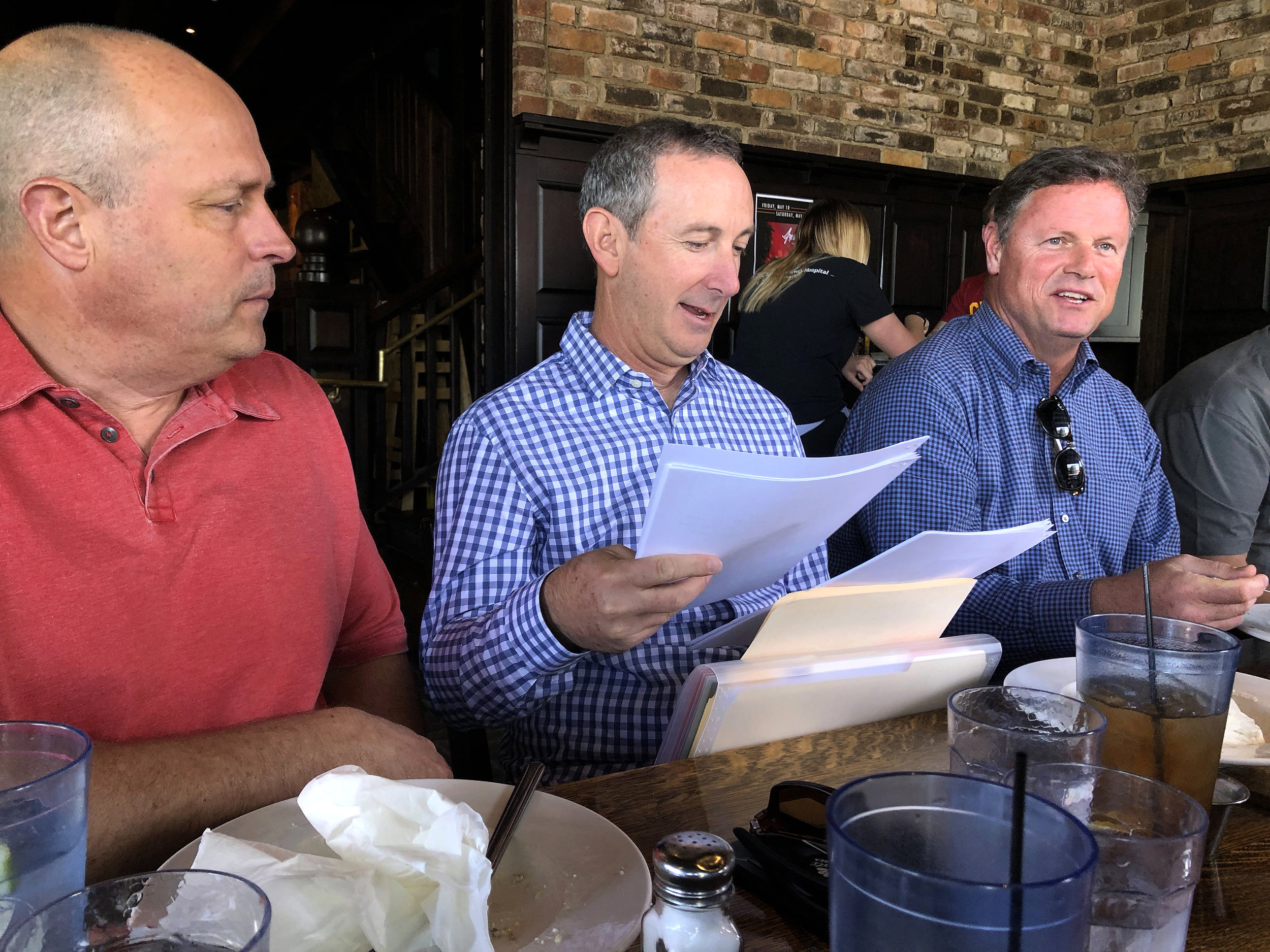 Matt Maiocco (center) sorts through letters from fans while sitting with Kirk Reynolds (left) and Lal Heneghan at lunch in Whitefish, Montana on May 20, 2018 before visiting Dwight Clark in his home.