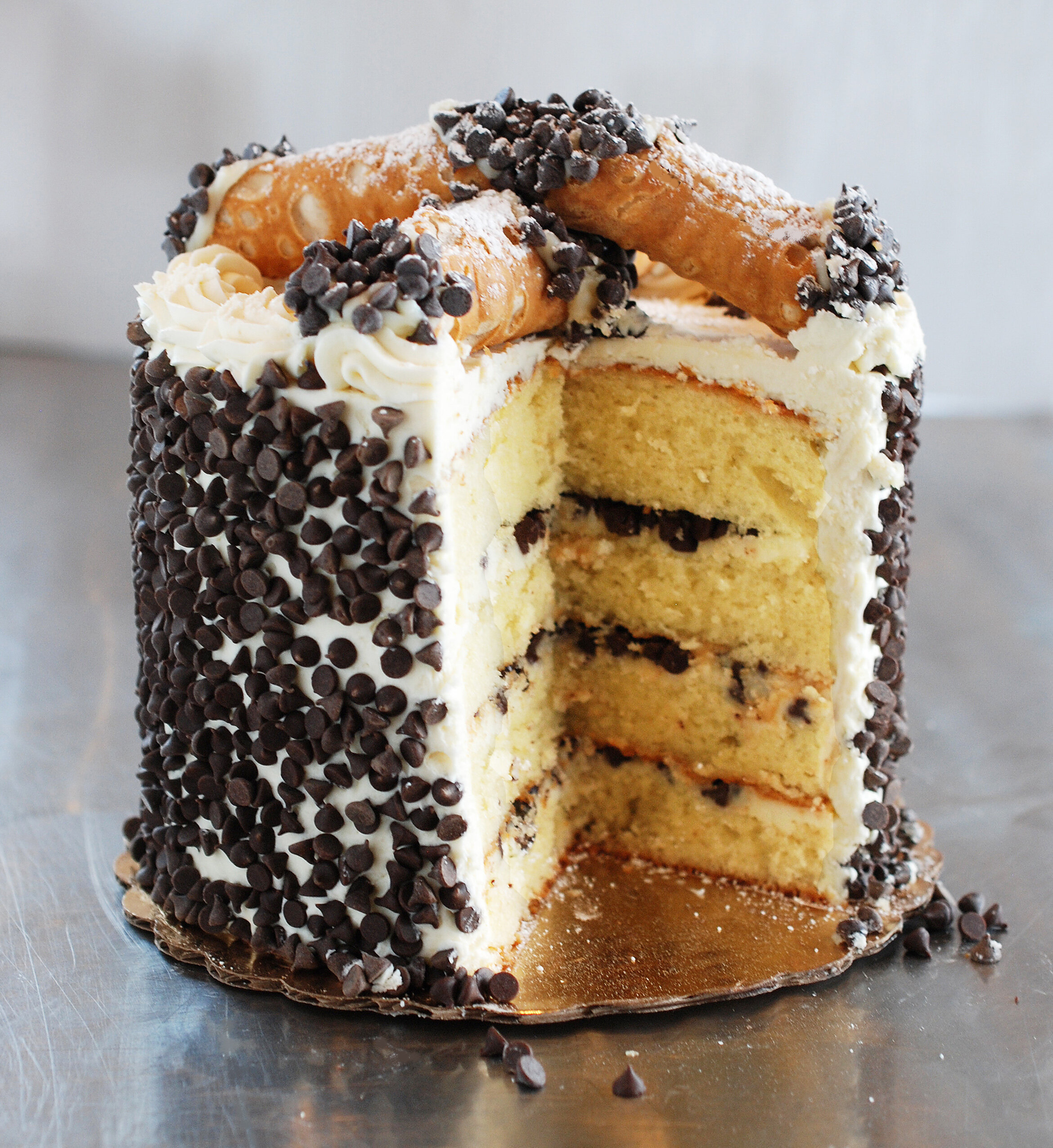 """CANNOLI CAKE - Layered sponge cake with classic New York cream filling topped with fresh cannoli and mini chocolate chips. Need one-week advanced notice. Available for pick-up at our Seattle location.6"""" $408"""" $6010"""" $80CALL FOR PRICING ON LARGE CAKES"""