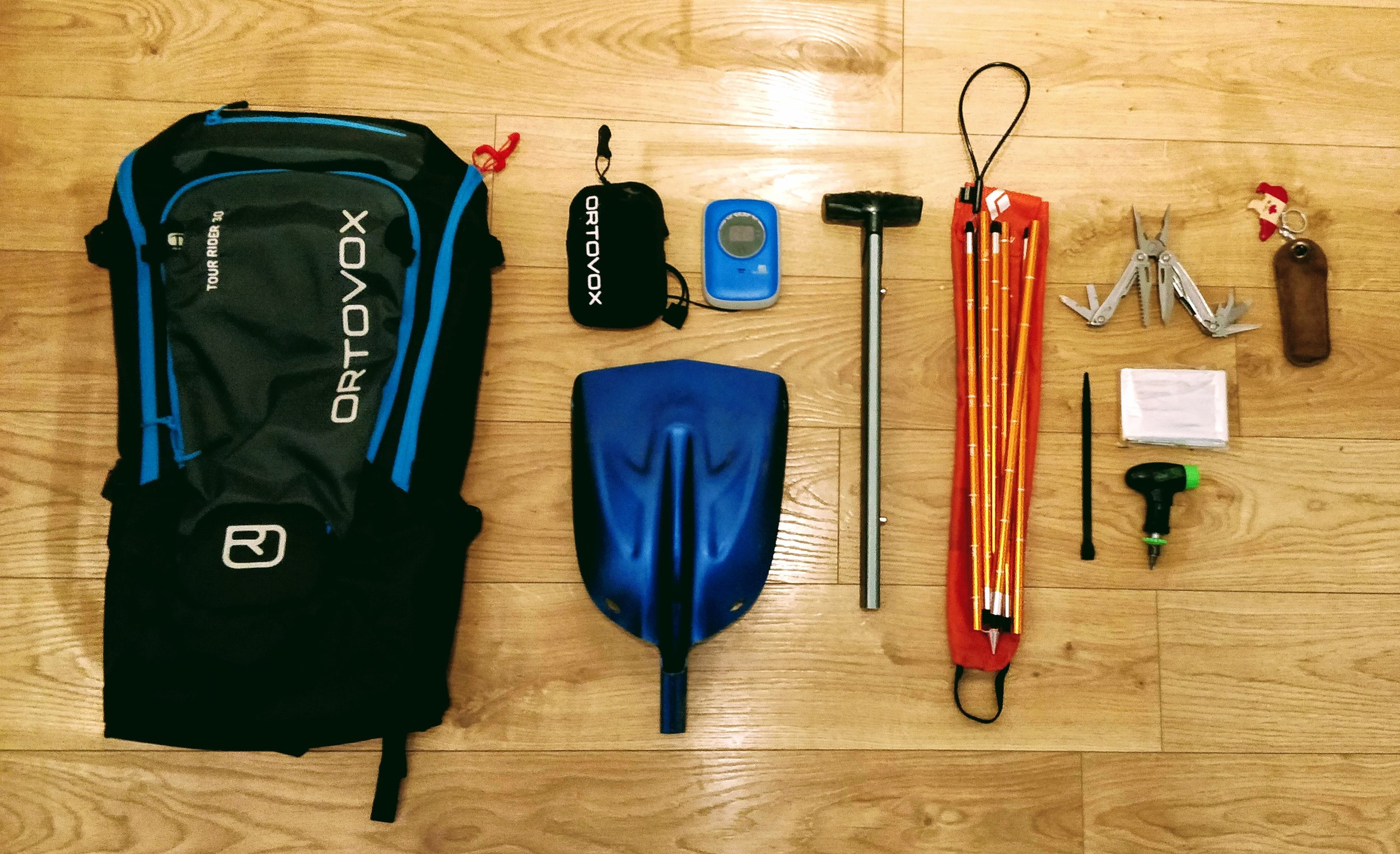 Basic safety gear, from left: 30l backpack, 3 antenna transceiver, shovel head, shovel handle, 265cm tour probe, Leatherman multitool, foil blanket, cable tie, and snowboard tool