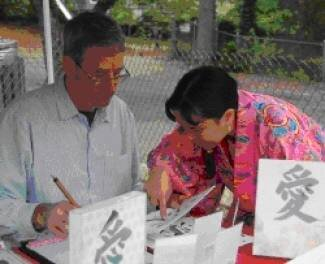 Peter Holden, of Bowie, gets a crash course in Japanese calligraphy at the Japan-Aid Festival