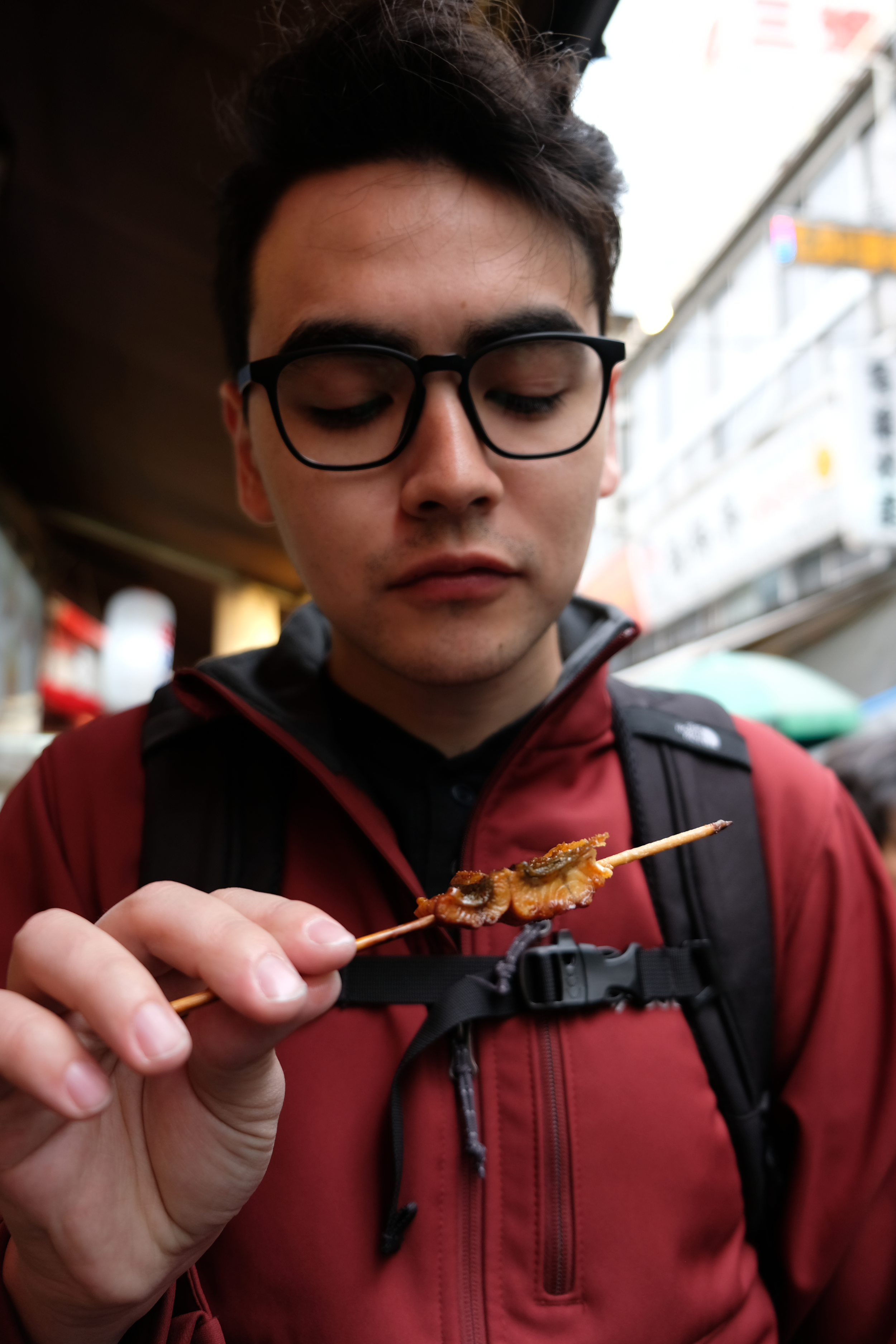 Topher enjoying unagi (eel) on a stick at the Tsukiji Market in Tokyo