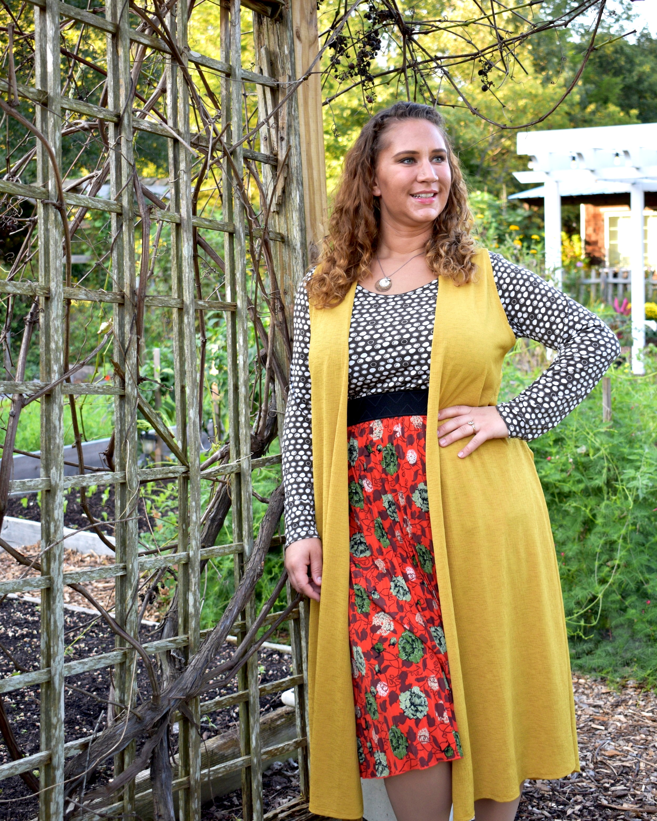 Nice balance of pattern here using a textured polka dot and chiffon floral skirt with the micro pleats. The textured mustard vest compliments the green and orange tones in the skirt.