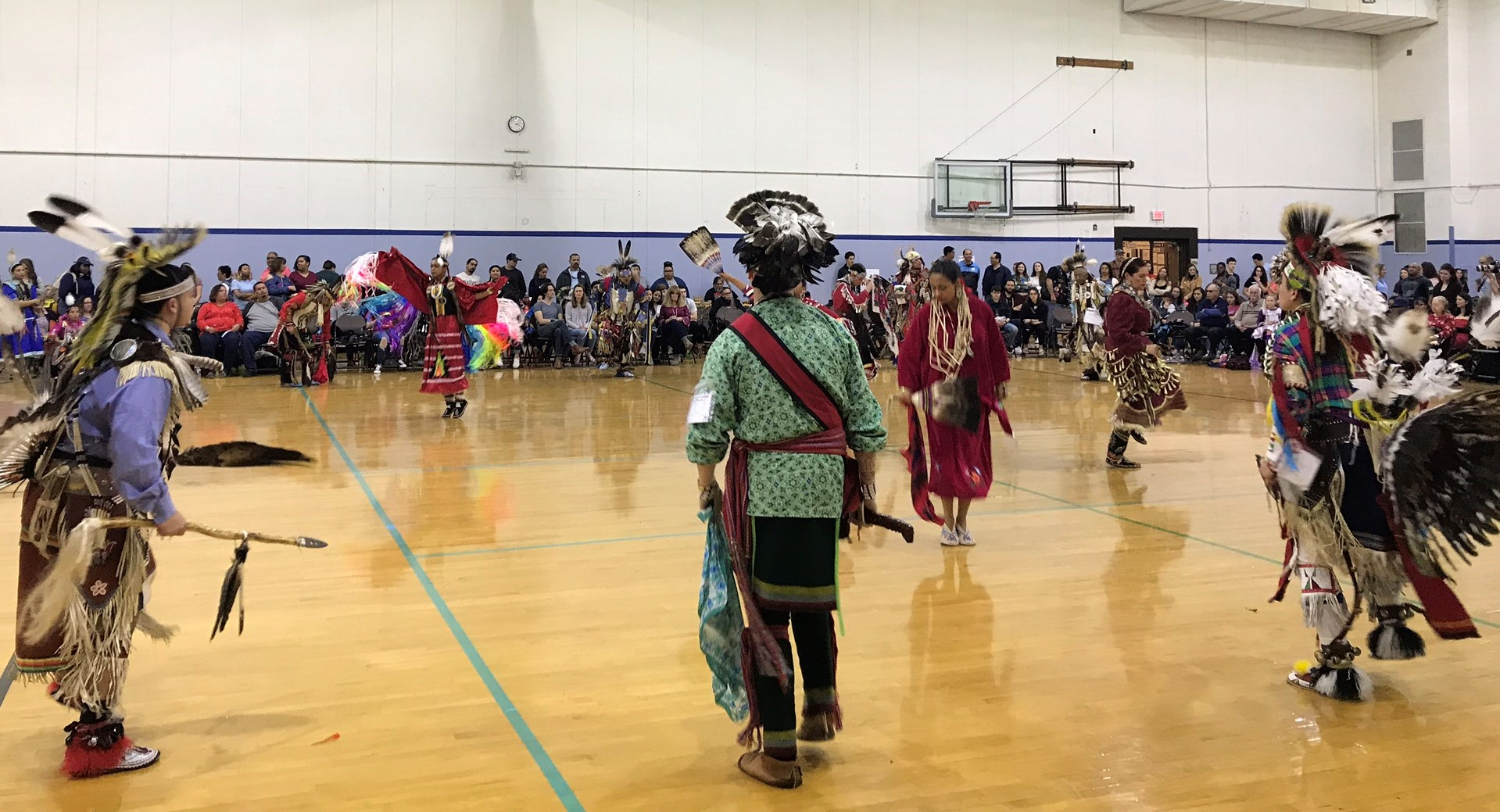 Final round contest during the Red Dress Special. Teen and adult men's traditional dancers standing guard around the parameter.