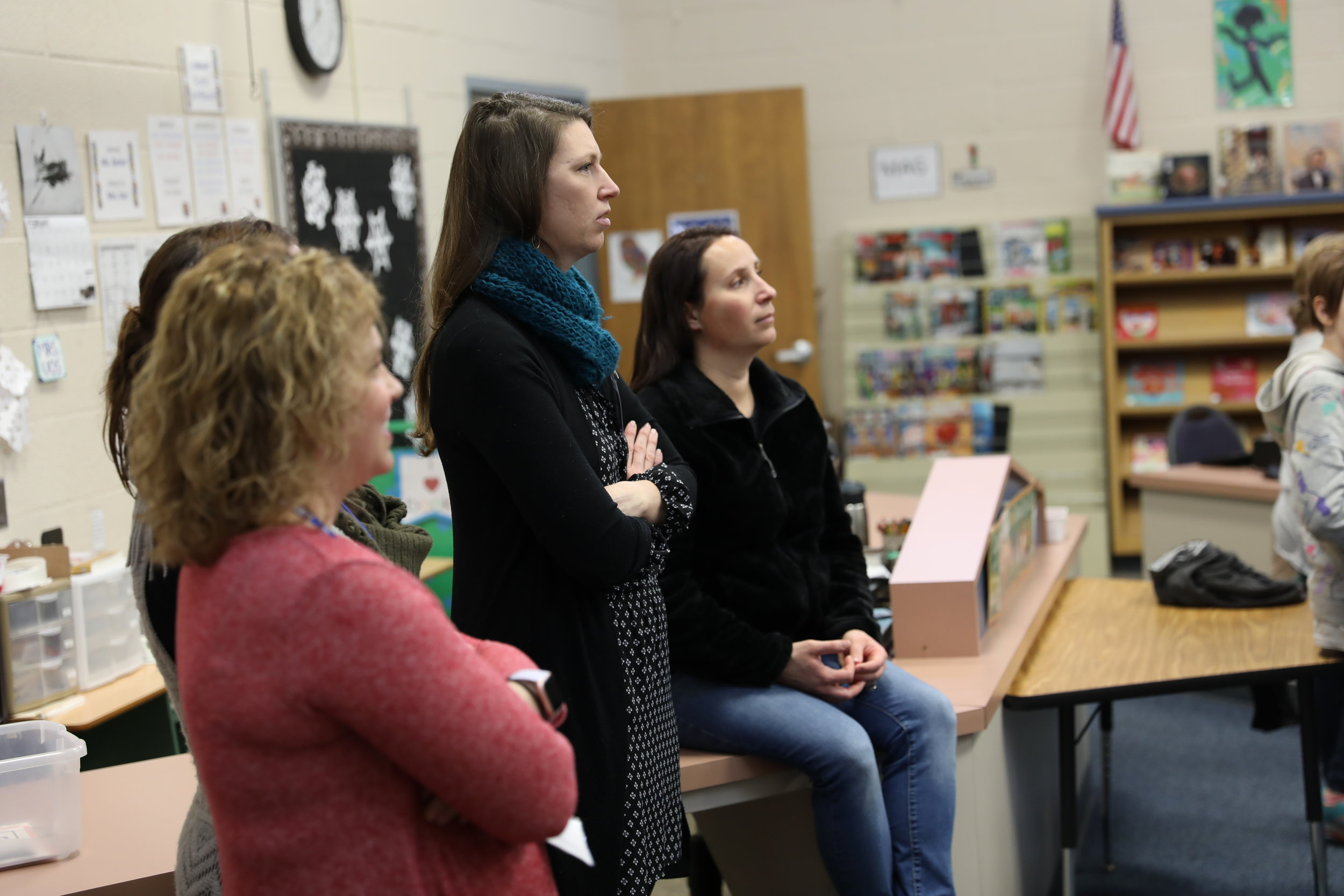 Parents listen to a teacher's instructions to be prepared to help students.