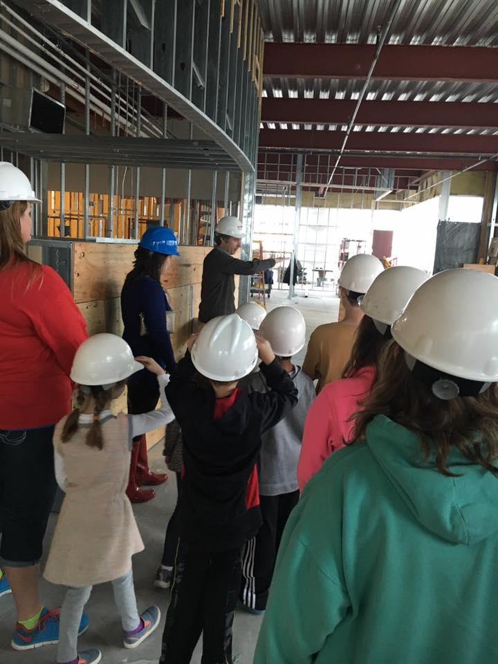 A parent takes students on a tour of one of his building projects to explain his role as an architect.