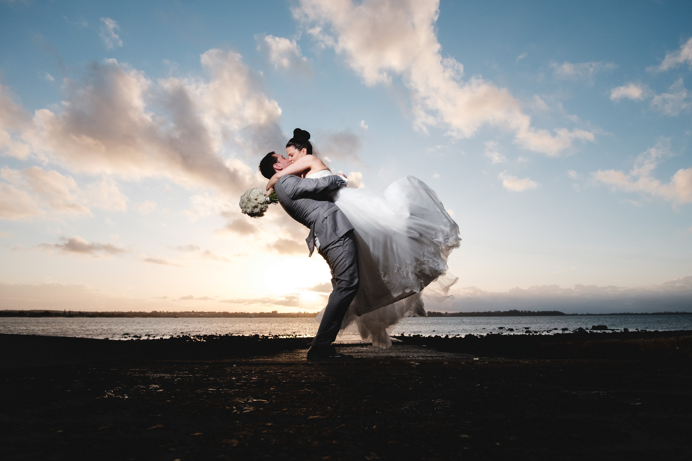 bride and groom kissing with stunning sunset at Redlands, brisbane. fun, relaxed adventurous wedding photography gold coast