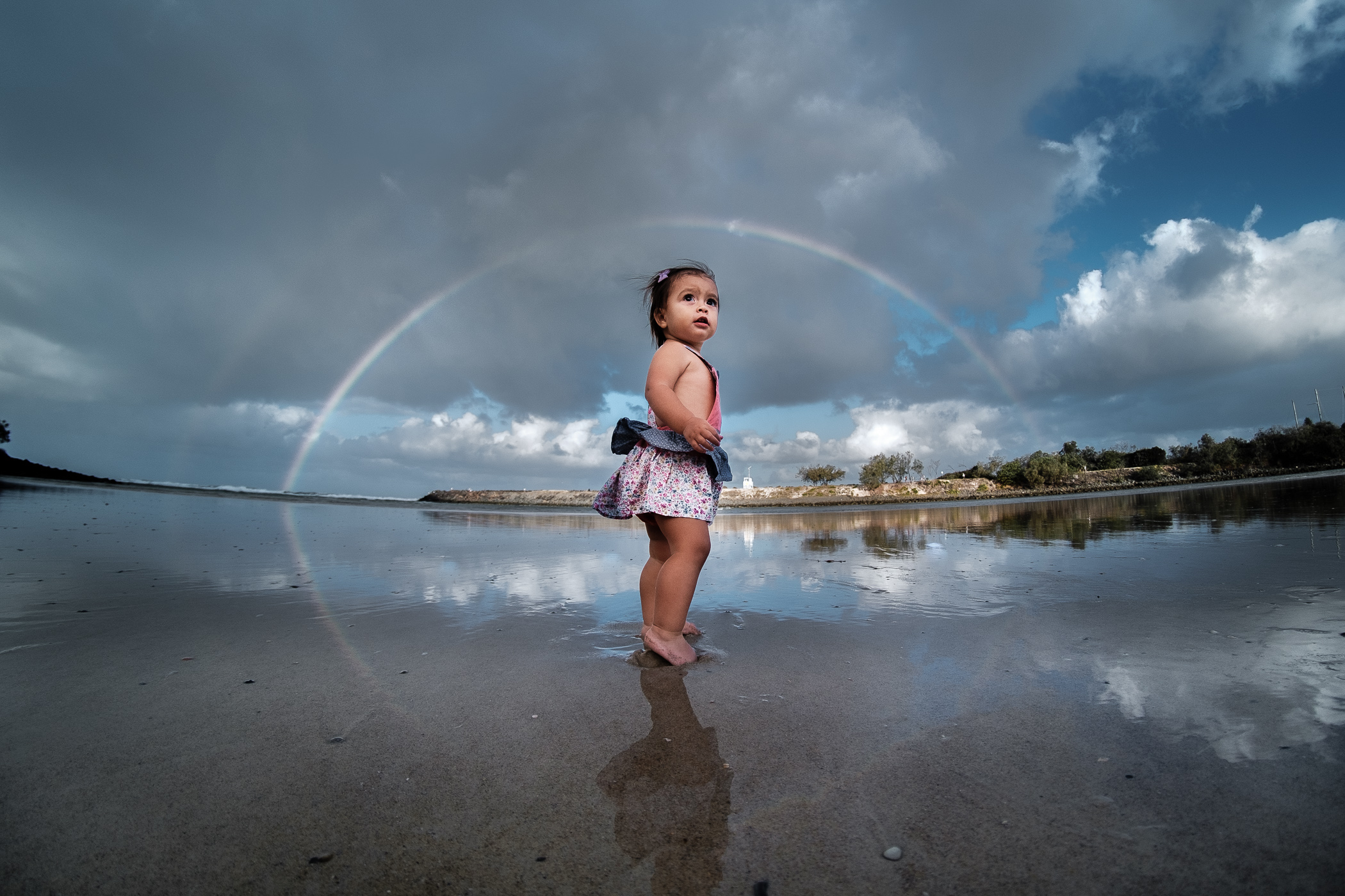 child playing at Tallebudgera creek at sunset with rainbow overhead. Relaxed fun gold coast family photography